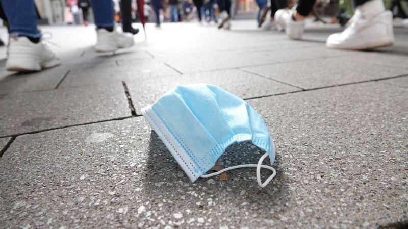 Ein auf dem Boden liegender Mund-Nasen-Schutz in der Kölner Innenstadt. Der Bund will eine ergänzende Maskenpflicht einführen. Symbolfoto: dpa/Peneshko