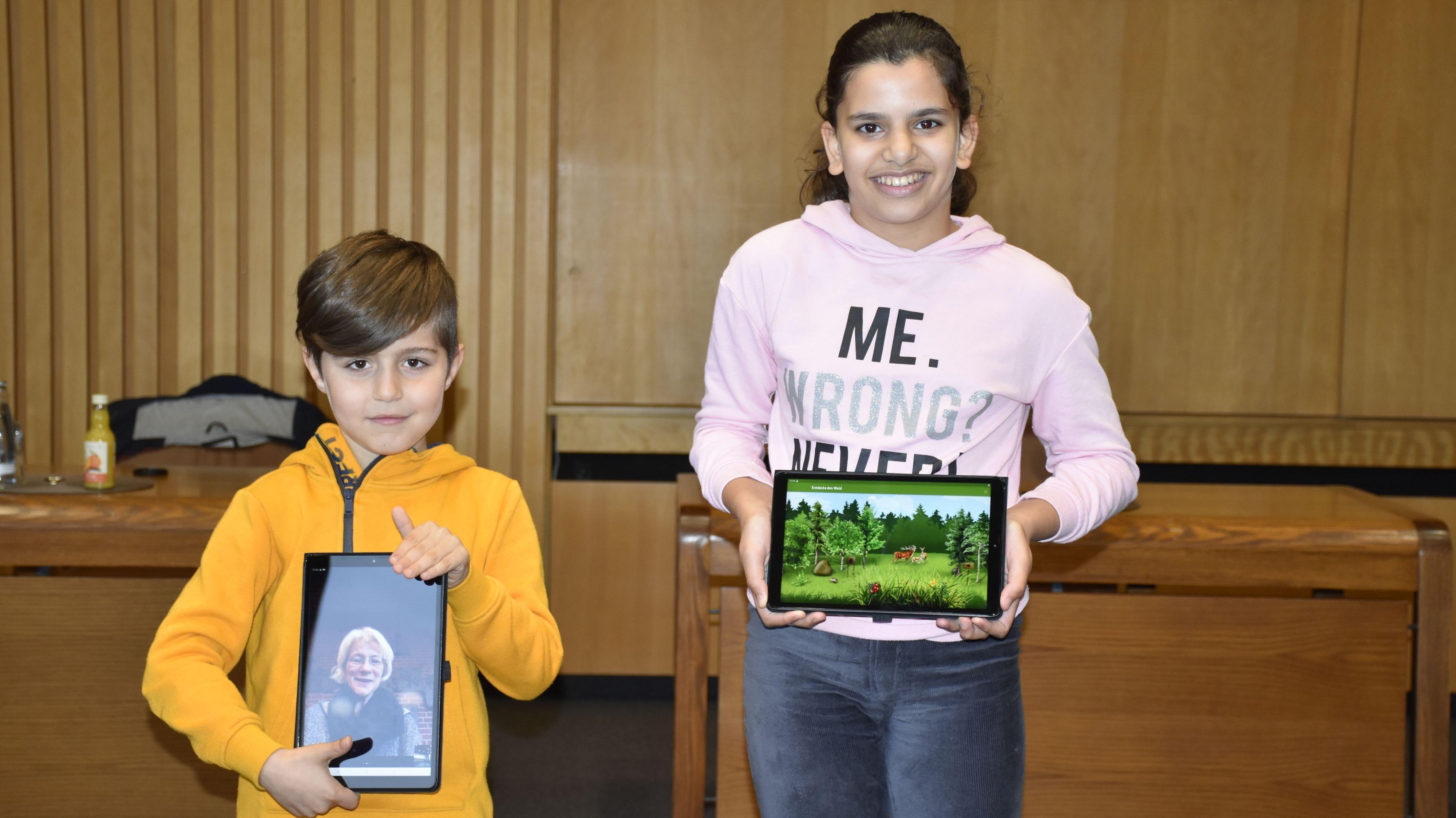 In einer Zoom-Konferenz sollen die Kinder jeden morgen zusammentreffen. Stolz zeigen Dalksh und Hala ihre Tablets. Foto: Scholz