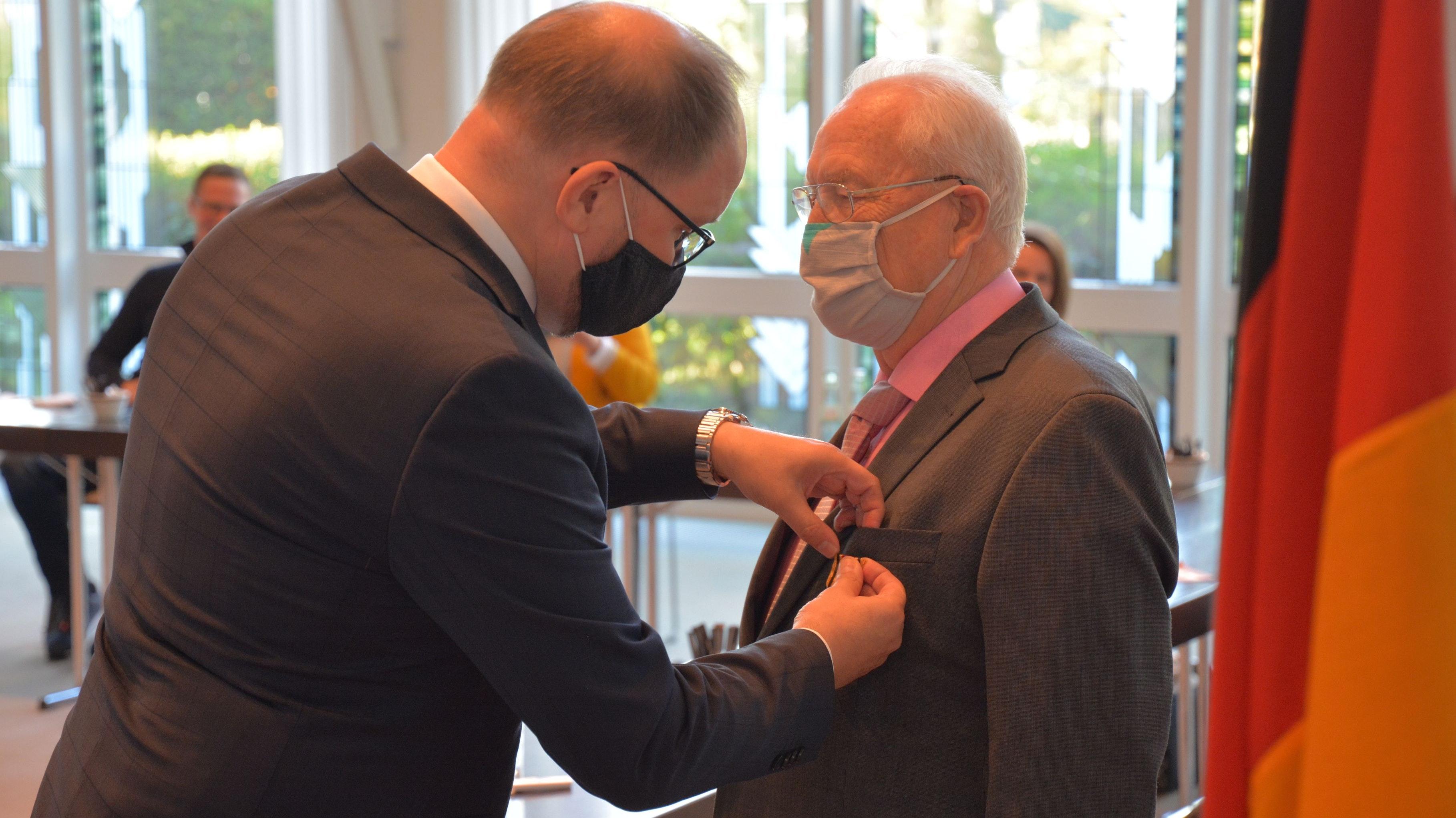 Hohe Auszeichnung: Landrat Johann Wimberg steckt Erich Behlau das Bundesverdienstkreuz an. Foto: Hermes