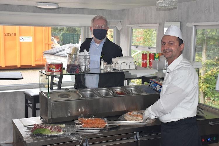 Die zart-gegrillten Hähnchenspieße zählen zu seinen Favoriten: Franz-Josef Lamping (hinten) verbindet einen Besuch in Mores Grill meist mit einem Essen. Inhaber Mores Aad (vorne) hat aber noch mehr Speisen zur Auswahl. Foto: Ferber