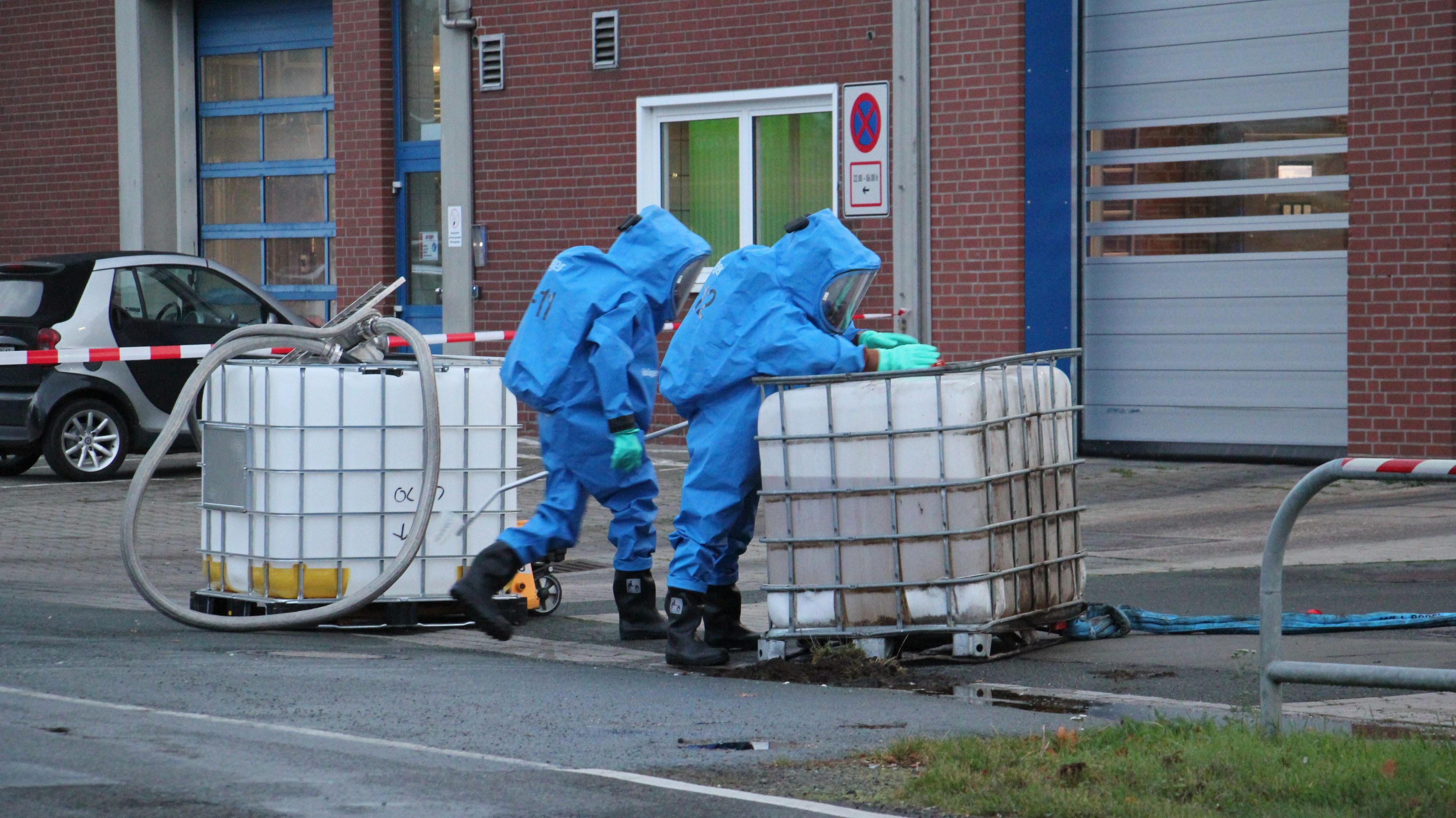 Einsatz mit Schutzanzügen: Zwei Feuerwehrkräfte pumpen die Flüssigkeit aus dem beschädigten Behälter in einen Ersatztank um. Foto: Speckmann