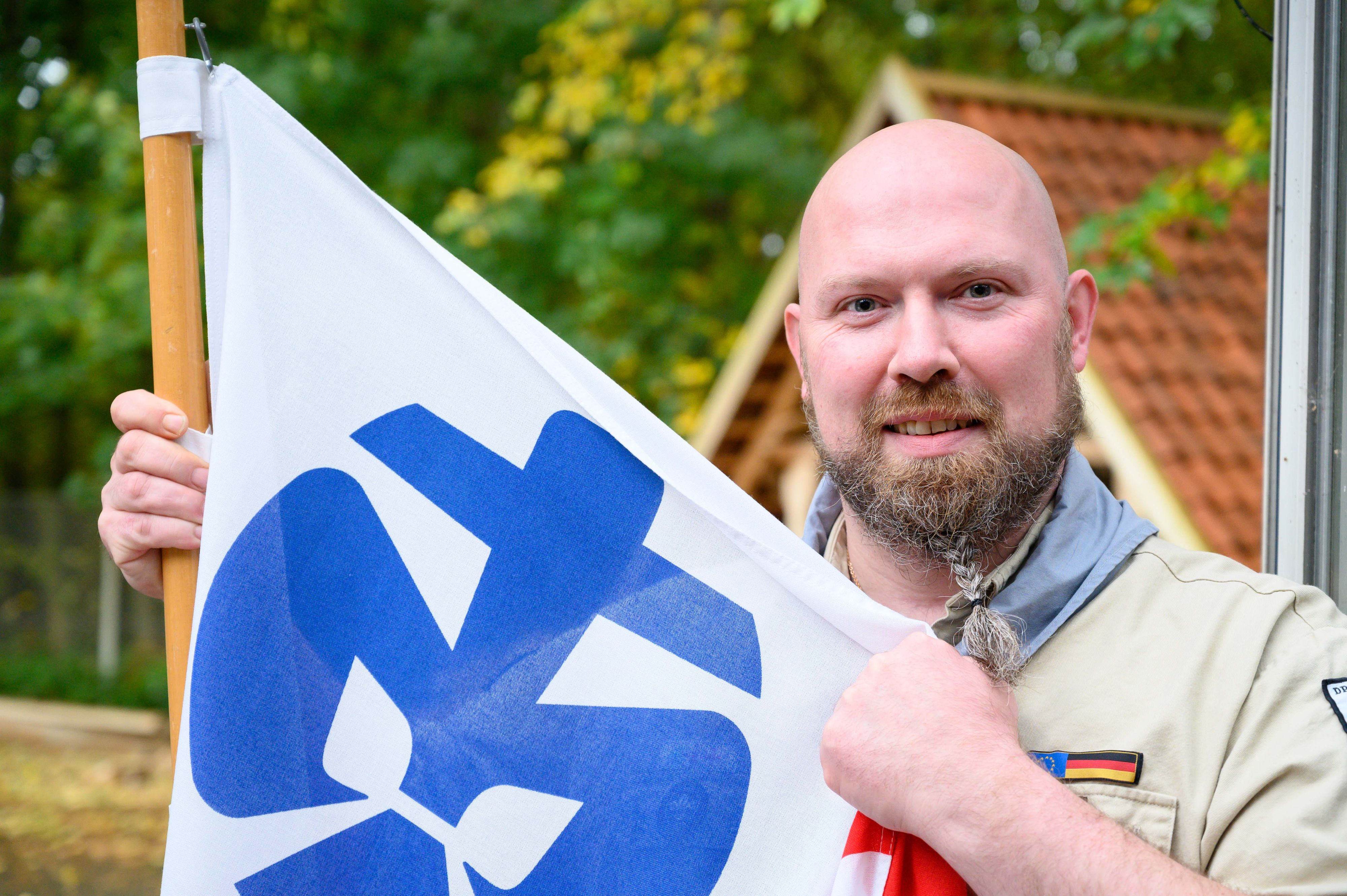 Wünscht allzeit gut Pfad: Thomas Schirmer mit Banner und Lilie der Pfadfinder. Foto: M. Niehues