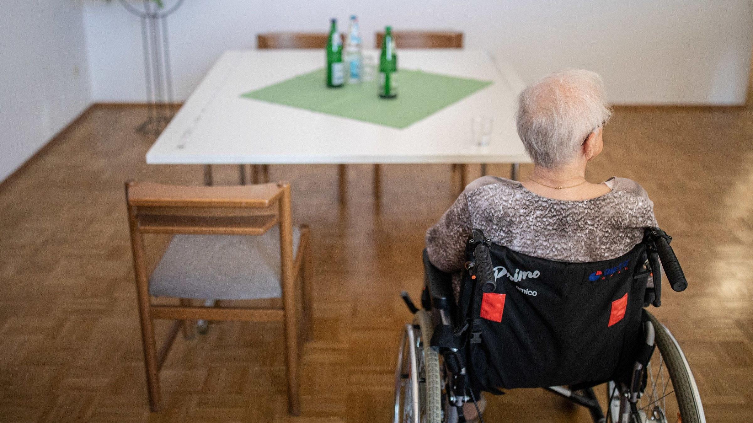 Einsam in Corona-Zeiten: Eine ältere Frau sitzt in einem Pflegeheim in ihrem Rollstuhl vor einem Tisch. Bild: Kusch/dpa