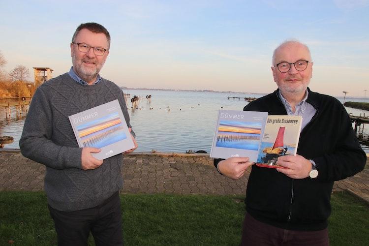 """Im Olgahafen: Willi Rolfes (links) und Andreas Kathe stellen ihr Buch Dümmer"""" mit dem See im Hintergrund vor. Foto: Lammert"""