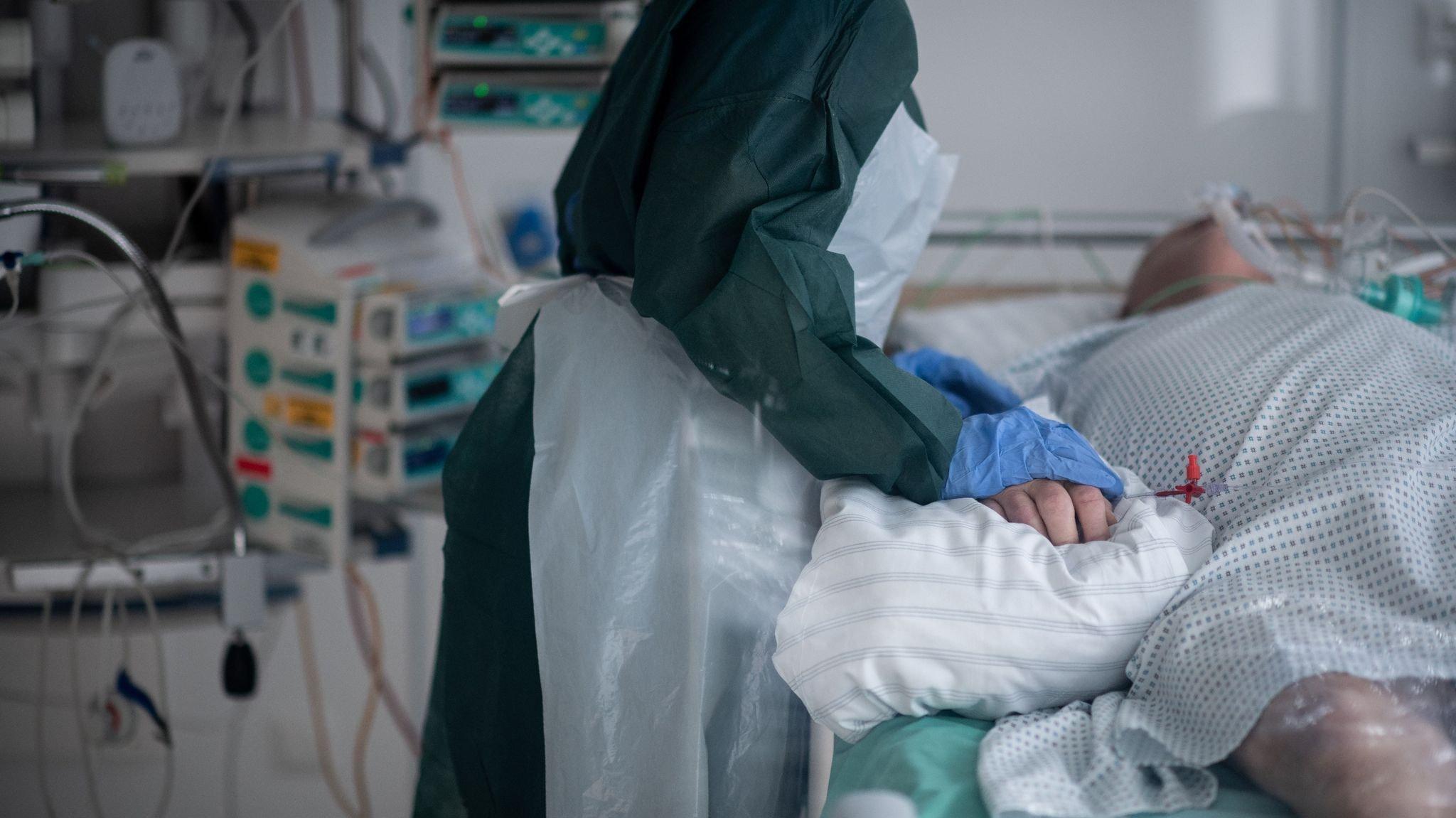 Eine Mitarbeiterin der Pflege in Schutzausrüstung betreut einen Corona-Patienten. Symbolfoto: dpa