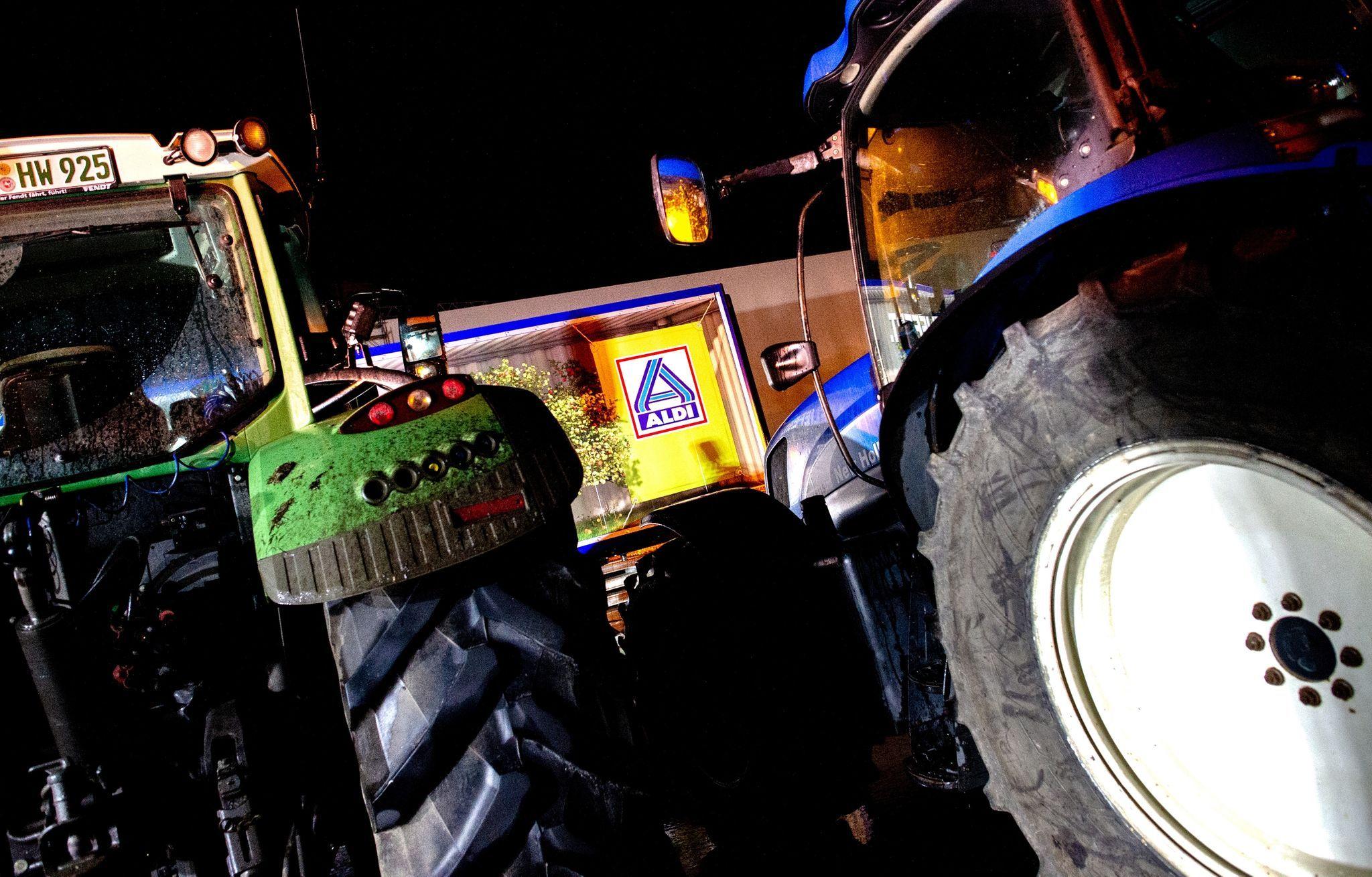 Traktoren stehen vor einem Lkw in der Zufahrt zum Zentrallager von Aldi. Foto: dpa/Dittrich