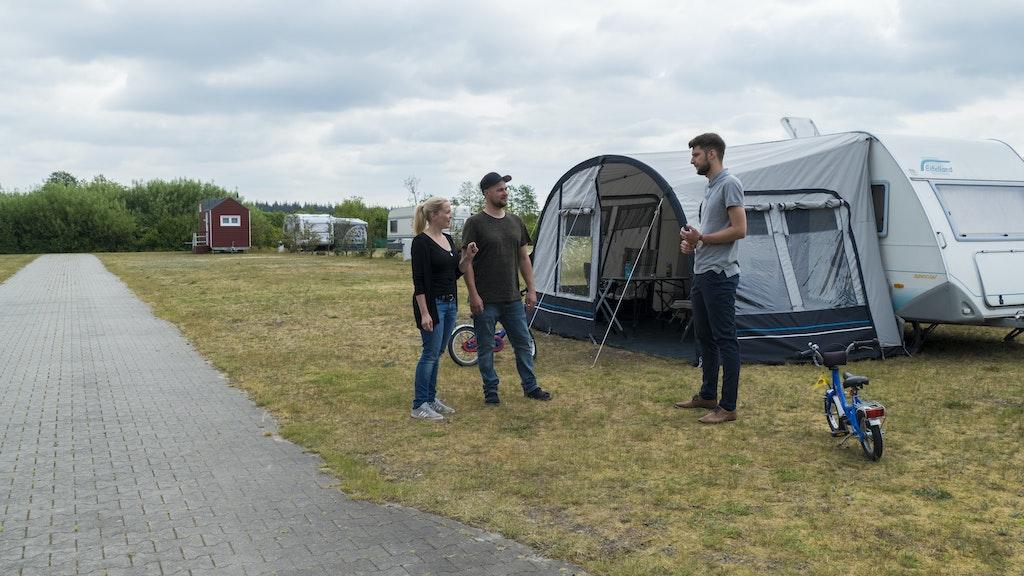 Abstand halten: Campingplatzbetreiber Max Wilken (rechts) informiert Gina und Marvin Gramberg, die mit ihren beiden Söhnen für eine Woche an der Thülsfelder Talsperre Urlaub machen, über die wichtigsten Hygieneregeln auf dem Campingplatz.  Foto: Stix