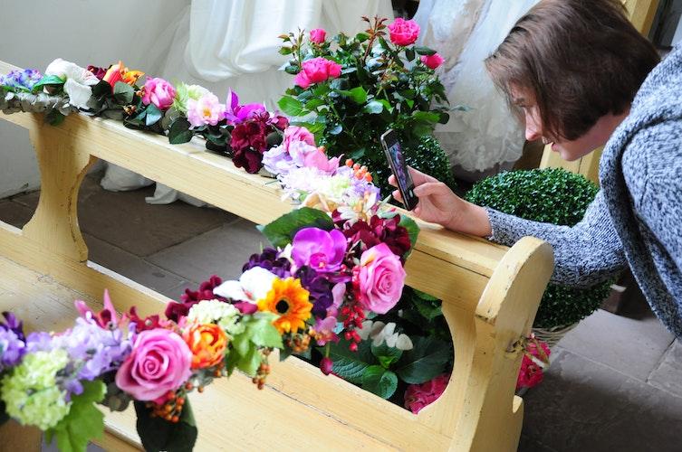 Den Blumenkranz ins Handy geholt: Doreen Richter aus Cloppenburg schießt ein Erinnerungsfoto in der Dorfkirche des Freilichtmuseums.