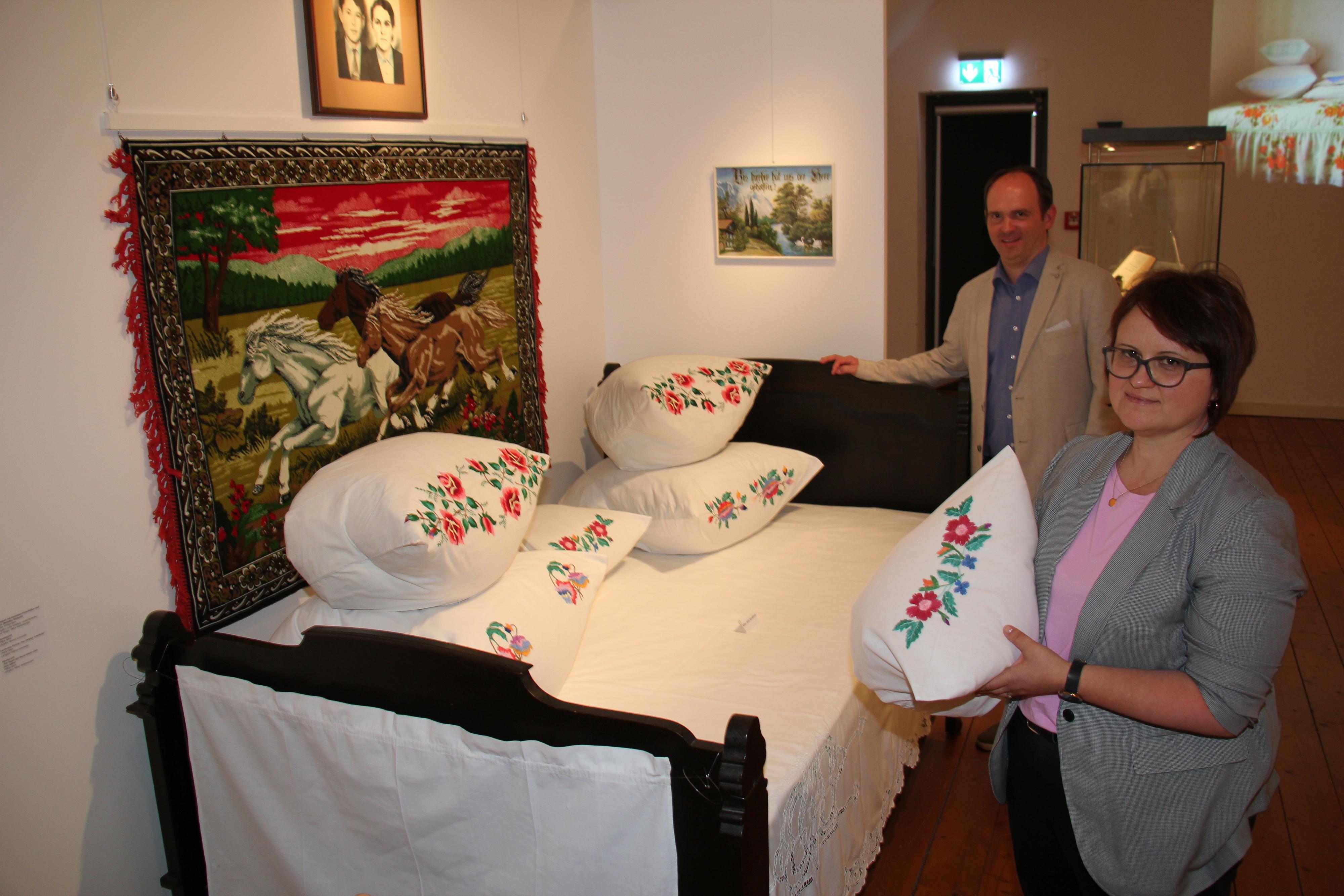 Das fein dekorierte Paradebett ist ein Hingucker der Ausstellung. Museumsleiter Kai Jansen und Kuratorin Marina Schmieder haben die Erinnerungsstücke der Spätaussiedler mit viel Bedacht und Kreativität zusammengestellt. Foto: Speckmann