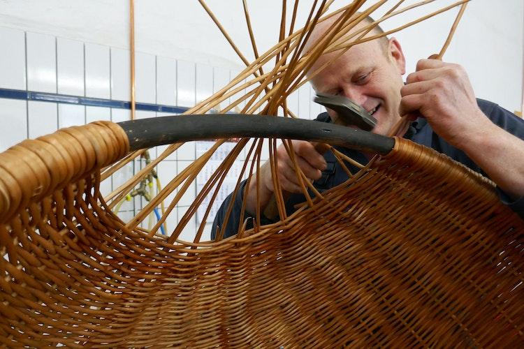 Keine leichte Arbeit: Heiko Stock am historischen Weidenstrandkorb. Foto: dpaNohrden