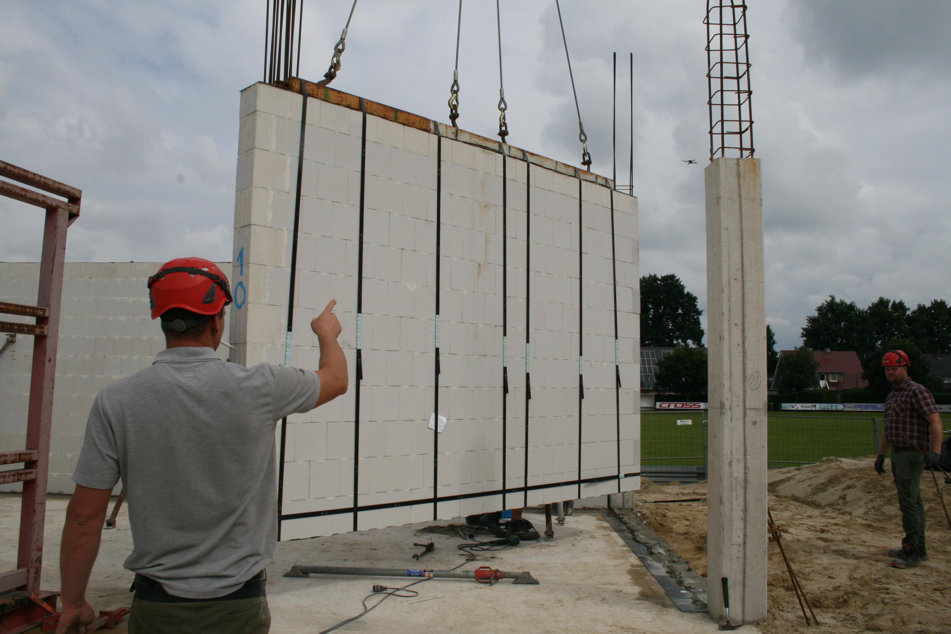 Maßarbeit: Die fertige Mauerwerkstafel hängt mit speziellen Traversen am Kran und kann so passgenau auf der Bodenplatte installiert werden.  Foto: © Gemeinde Emstek