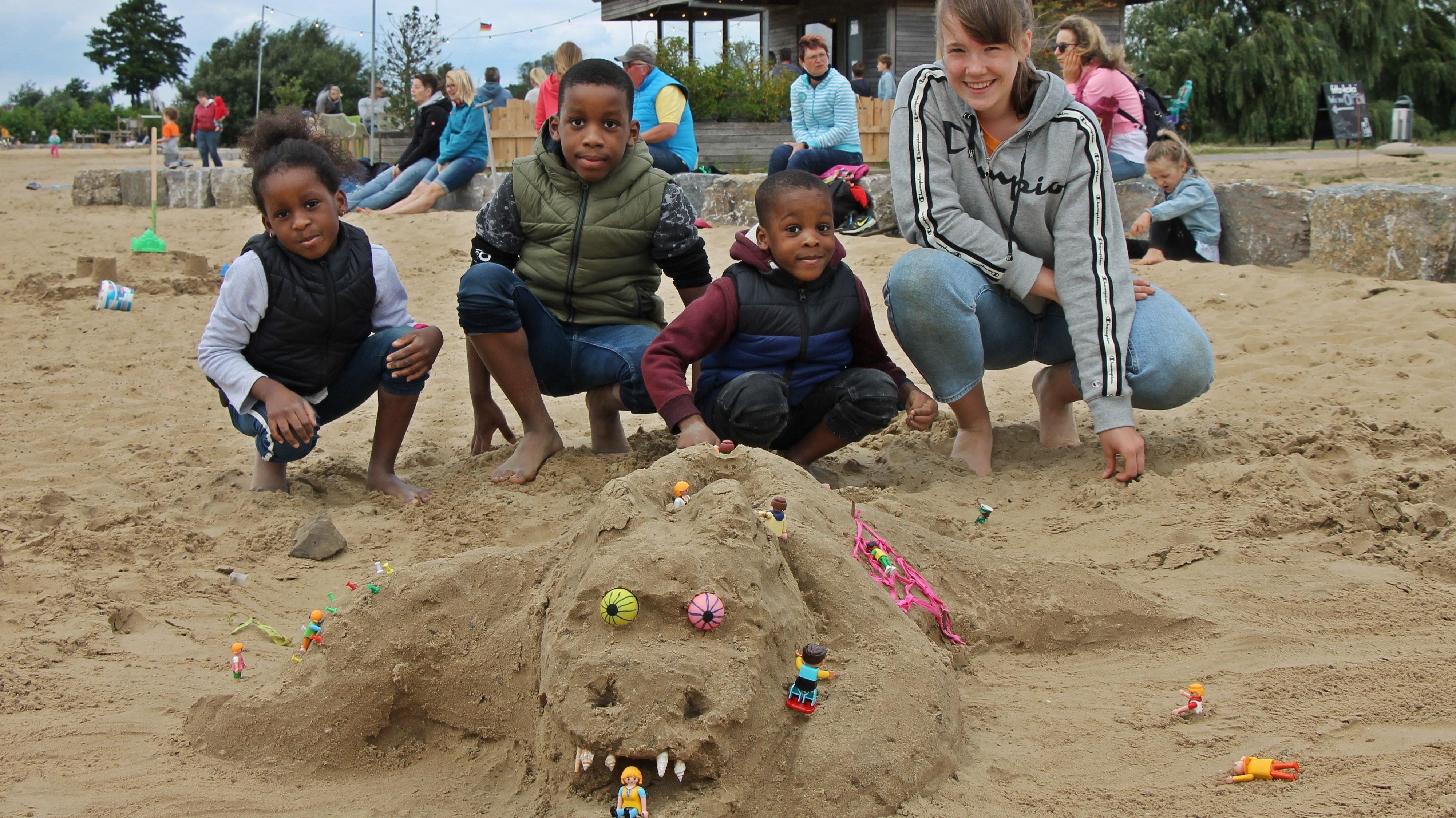 Gruseliges aus Sand: (von links) Rose, Samuel und David Kalu-Ogwa aus Vörden bauten das Monster, Greta Blömer aus Damme gab dem Trio Tipps. Foto: Oevermann