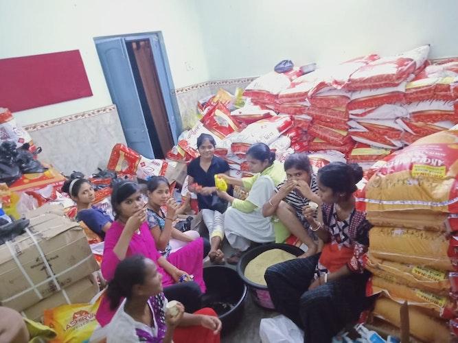 Straßenkinder in Kalkutta vor Bergen von Lebensmitteln: Sie helfen mit beim Verpacken der Pakete. Das gehört auch mit zur Lebensphilosophie: helfen und Verantwortung übernehmen. Foto: privat
