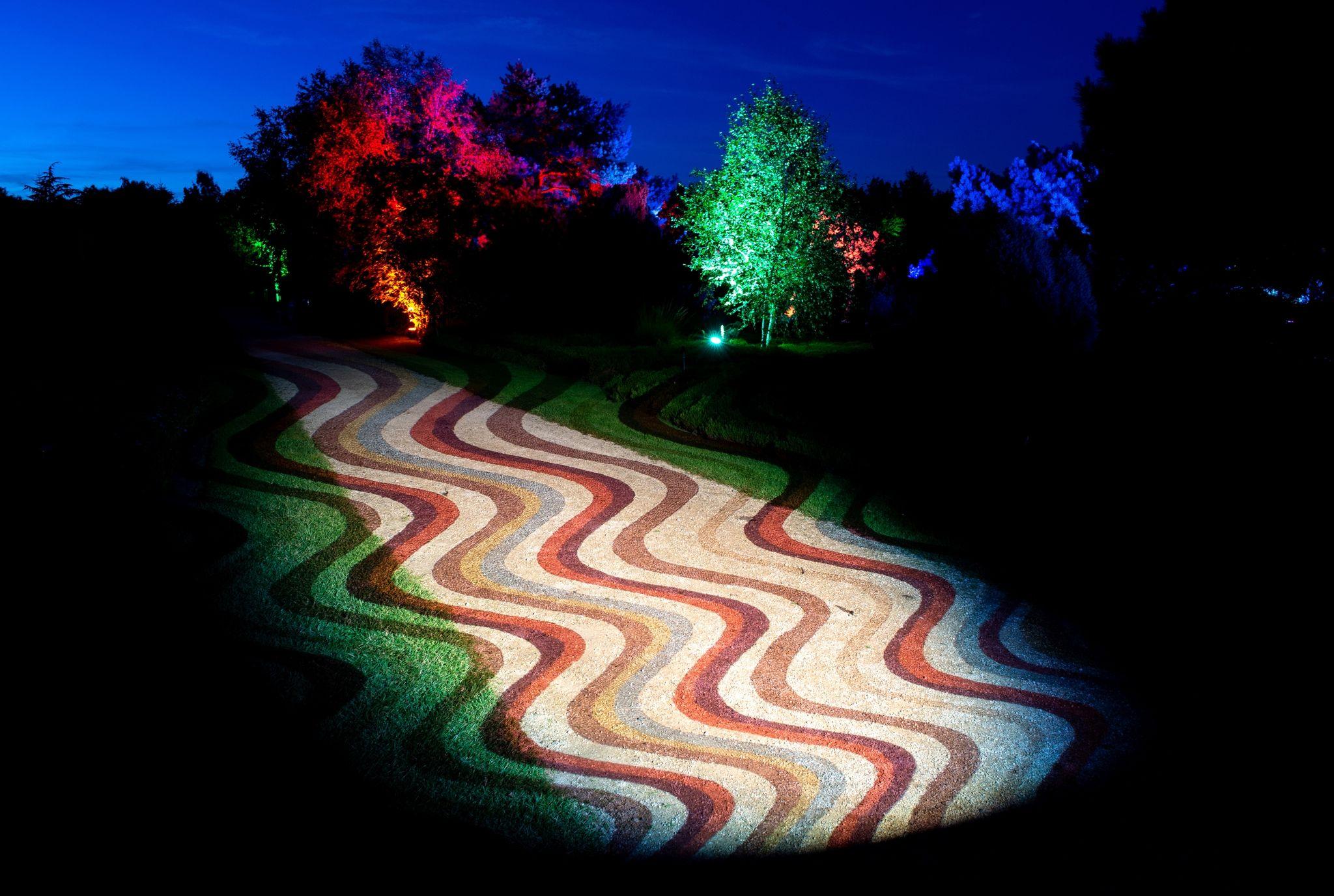 Wellenförmige Strukturen werden im Park der Gärten auf einen Weg projiziert. Foto: Hauke-Christian Dittrich / dpa