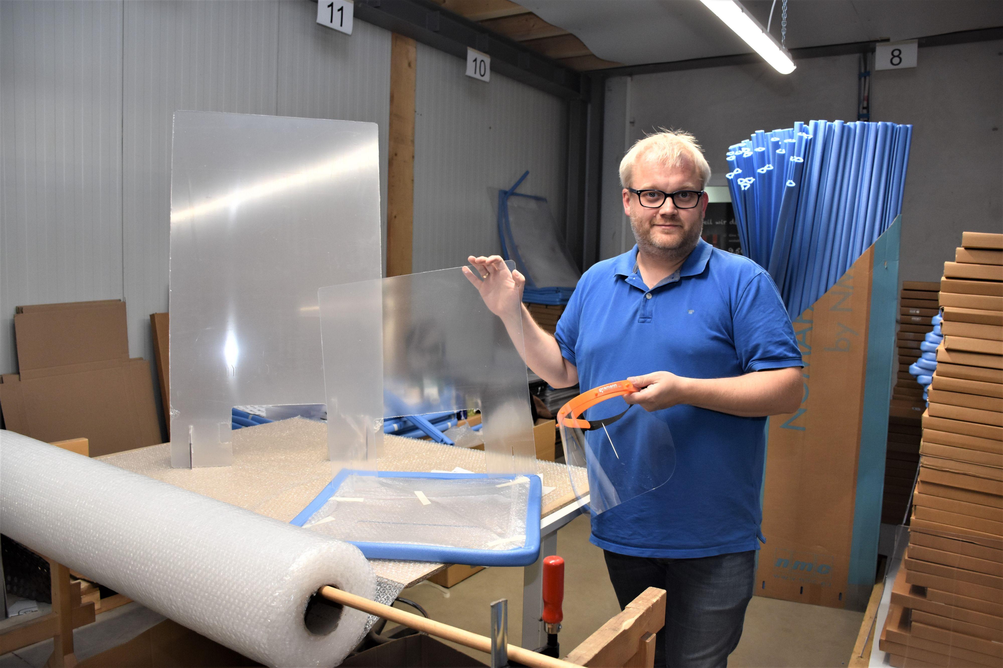 """Gramann-Vertriebschef Jan-Bernd Rolfes mit den """"Krisenprodukten"""" der Digitaldruckerei: Spuckschutzwand und Schutzvisier. Foto: Kühn"""