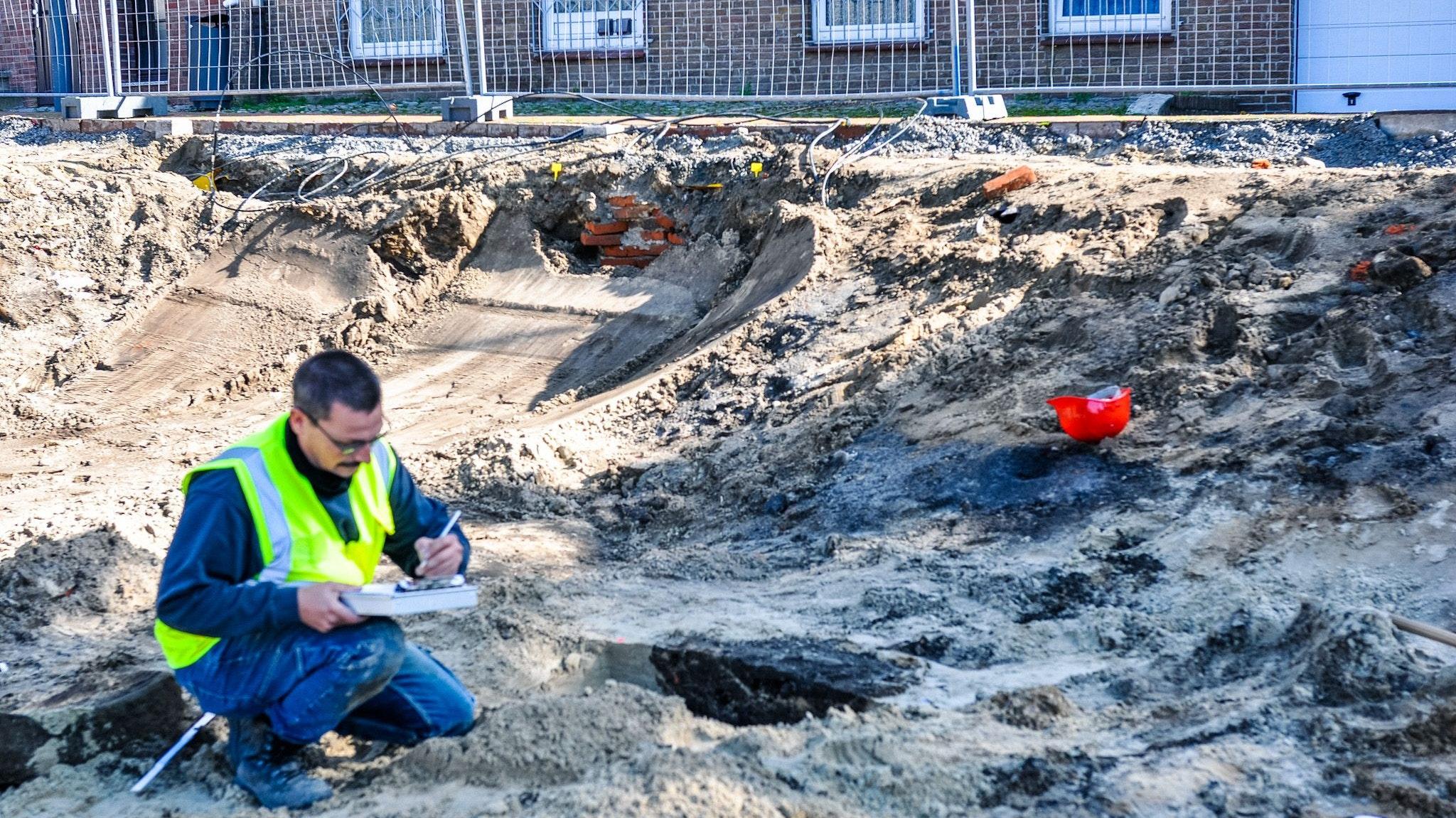 """DerArchäologe Falk Näth (""""Denkmal3D"""") dokumentiert und sichert die Funde in der Baugrube auf dem Grundstück ehemals Pundt/Schlarmann in der Lohner Innenstadt. Foto: Tombrägel"""