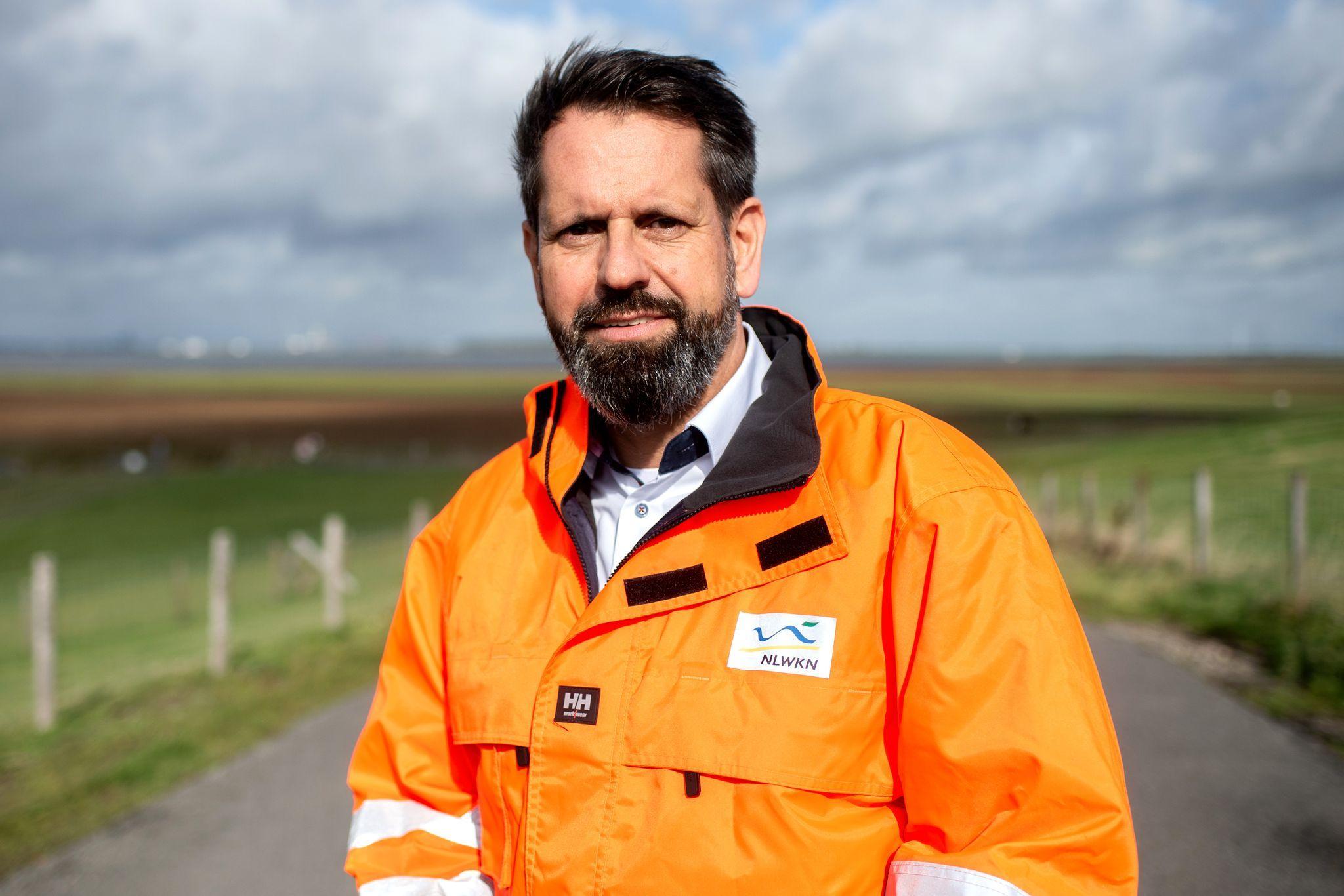 Olaf Lies (SPD), Umweltminister in Niedersachsen, steht auf dem Deich der Ems. Foto: Hauke-Christian Dittrich / dpa / Archiv