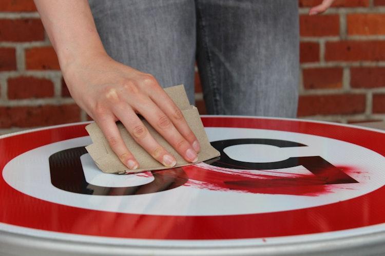 Ein Stück Pappe dient als Spachtel, um damit die gesprayte Farbe zu verteilen. Foto: Heinzel
