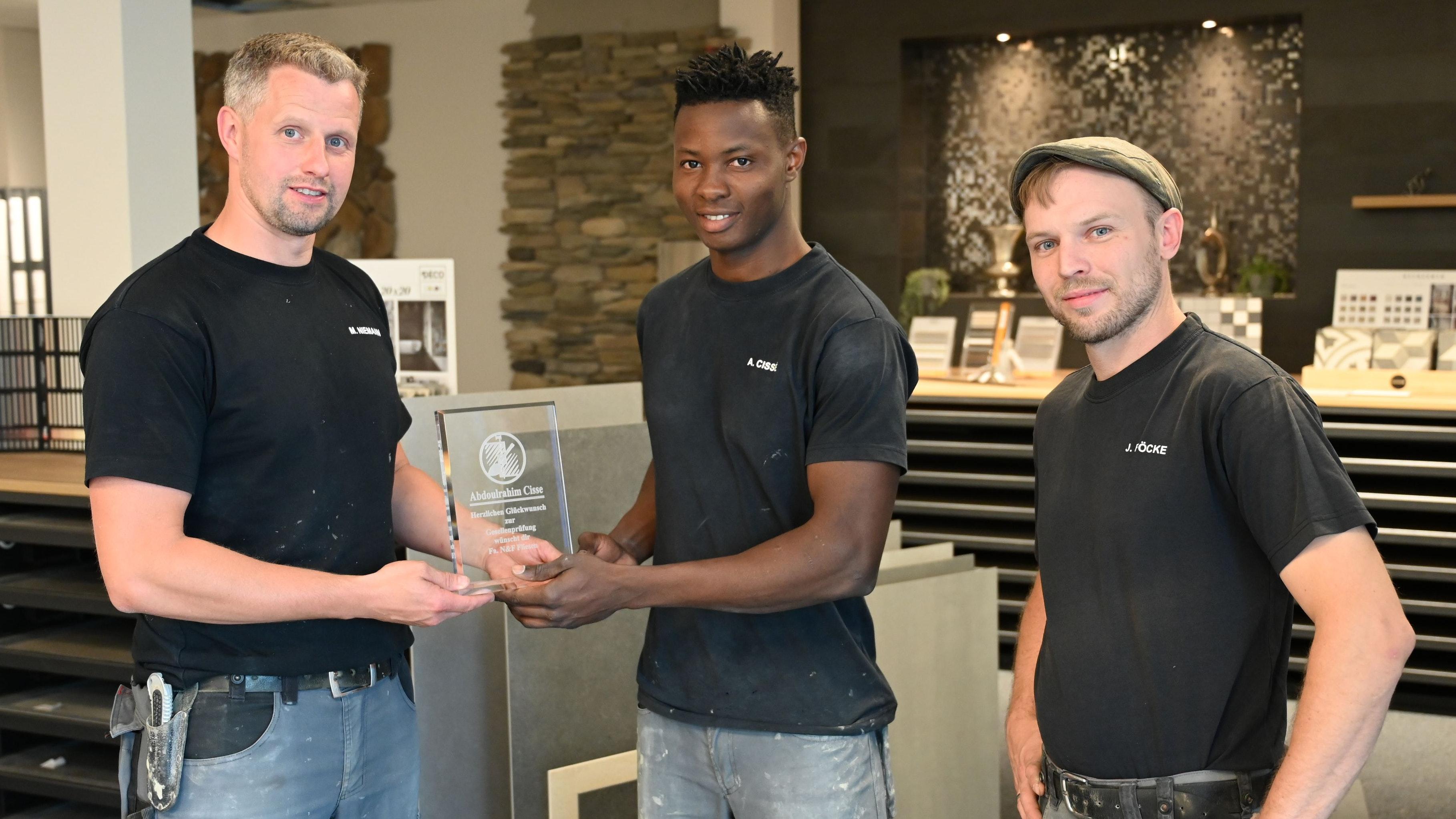 Auszeichnung: Die beiden Geschäftsführer Marcel Niemann (links) und Jörg Föcke (rechts) gratuliertenAbdulrahim Cissé. Foto: Hermes