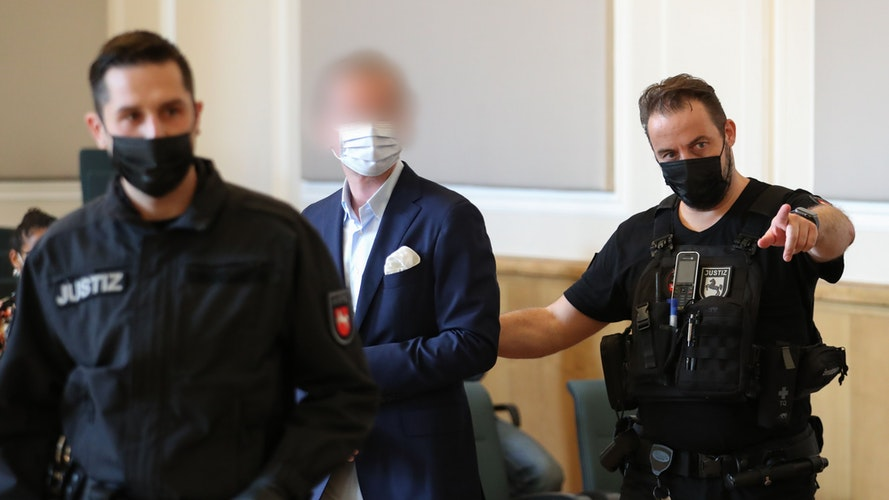 Ein Angeklagter wird von Justizbeamten in den Sitzungssaal vom Landgericht geführt: Insgesamt 5 Personen müssen sich wegen banden- und gewerbsmäßigen Betrugs verantworten. Foto: dpaGentsch