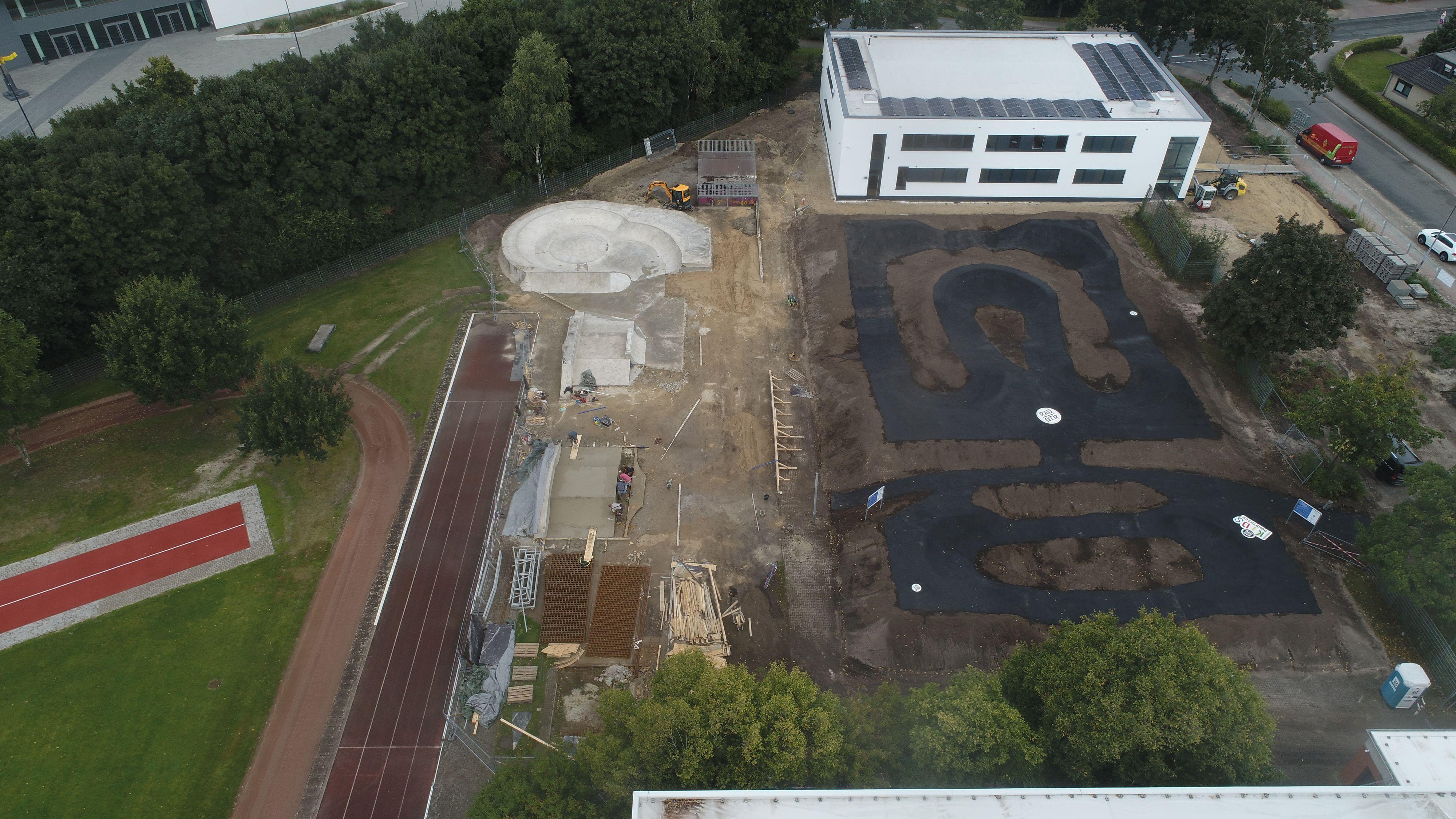 Die neue Anlage von oben: Links sind die Arbeiten an der Skateparksanierung zu sehen, rechts ist die Asphaltfläche des Pumptracks bereits fertiggestellt. Foto: RadQuartier GmbH
