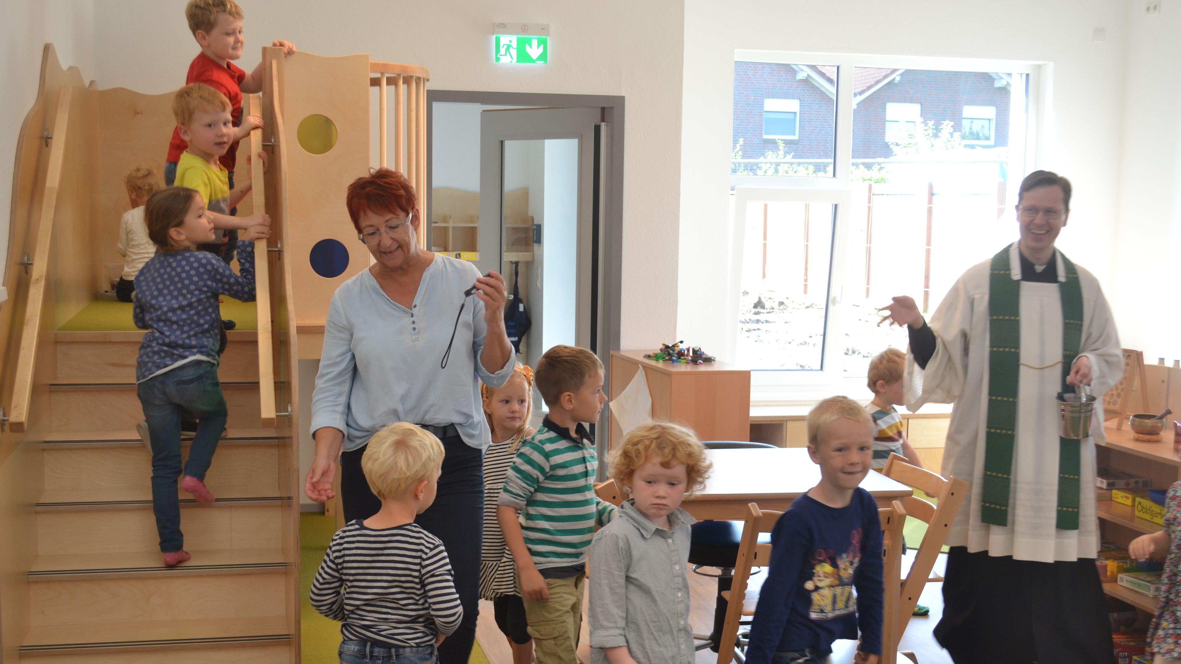 Einweihung: Pfarrer Jörn Illenseer und Kita-Mitarbeiterin Bernadette Thole gingen mit den Kindern durch die Räume. Foto: Schrimper