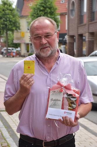 Regelmäßiger Blutspender: Peter Willenborg mit dem aktuellen Unfallhilfe- und Blutspendepass und dem Präsent der Dinklager Malteser. Foto: Böckmann
