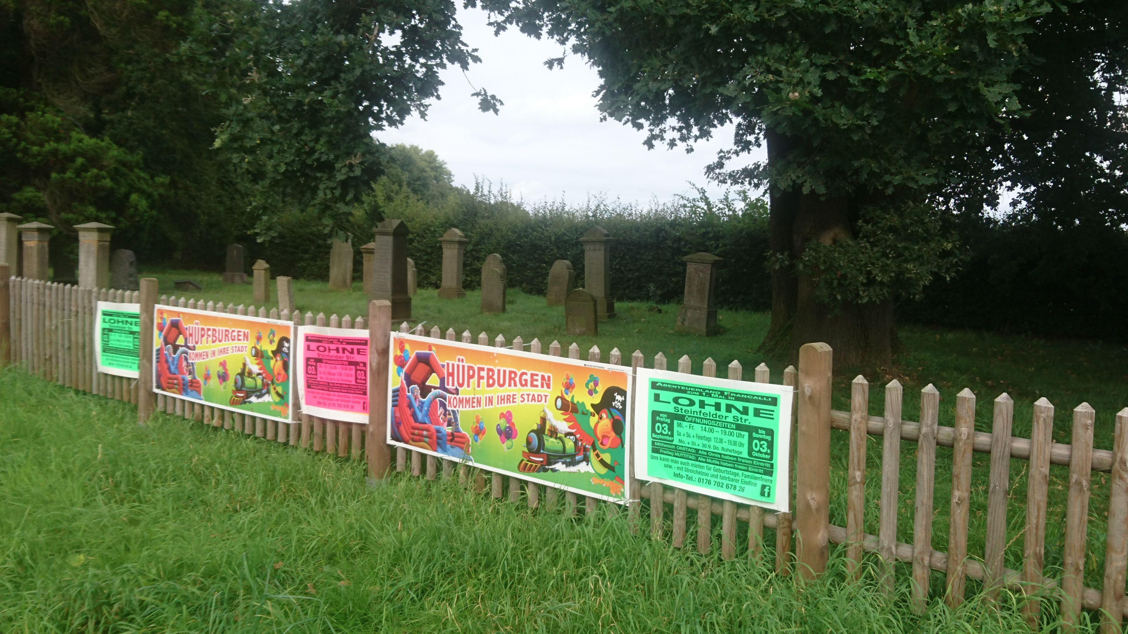 Reklame an der Ruhestätte: Am Zaun des jüdischen Friedhofs wurde für Hüpfburgen geworben. Foto: Speckmann