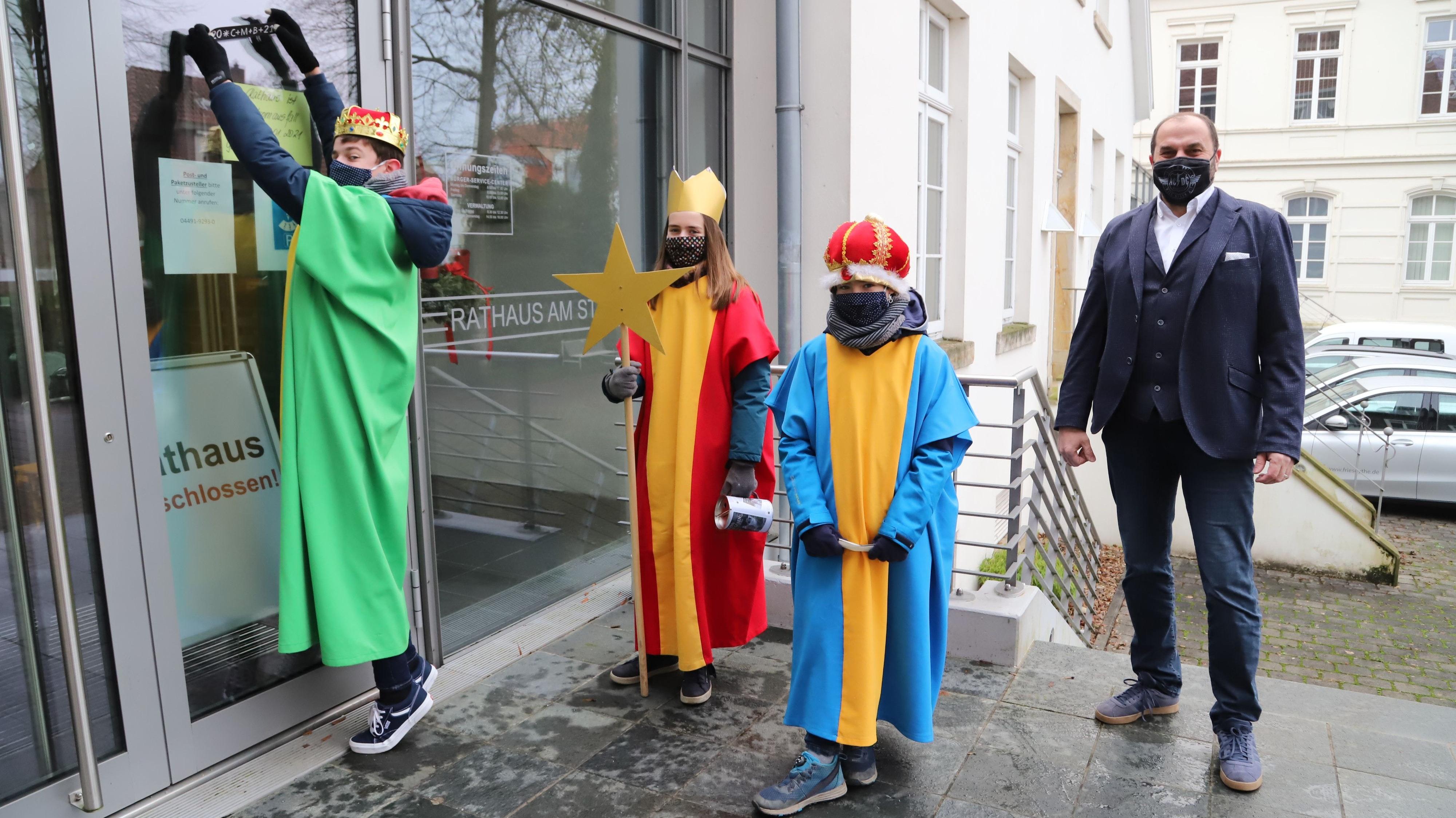 Eine Ausnahme: Die Sternsinger (von links) David,  Sarah und Aaron Fuhler besuchten Bürgermeister Sven Stratmann beim Rathaus und brachten den Segensspruch an der Eingangstür an.Foto: Passmann