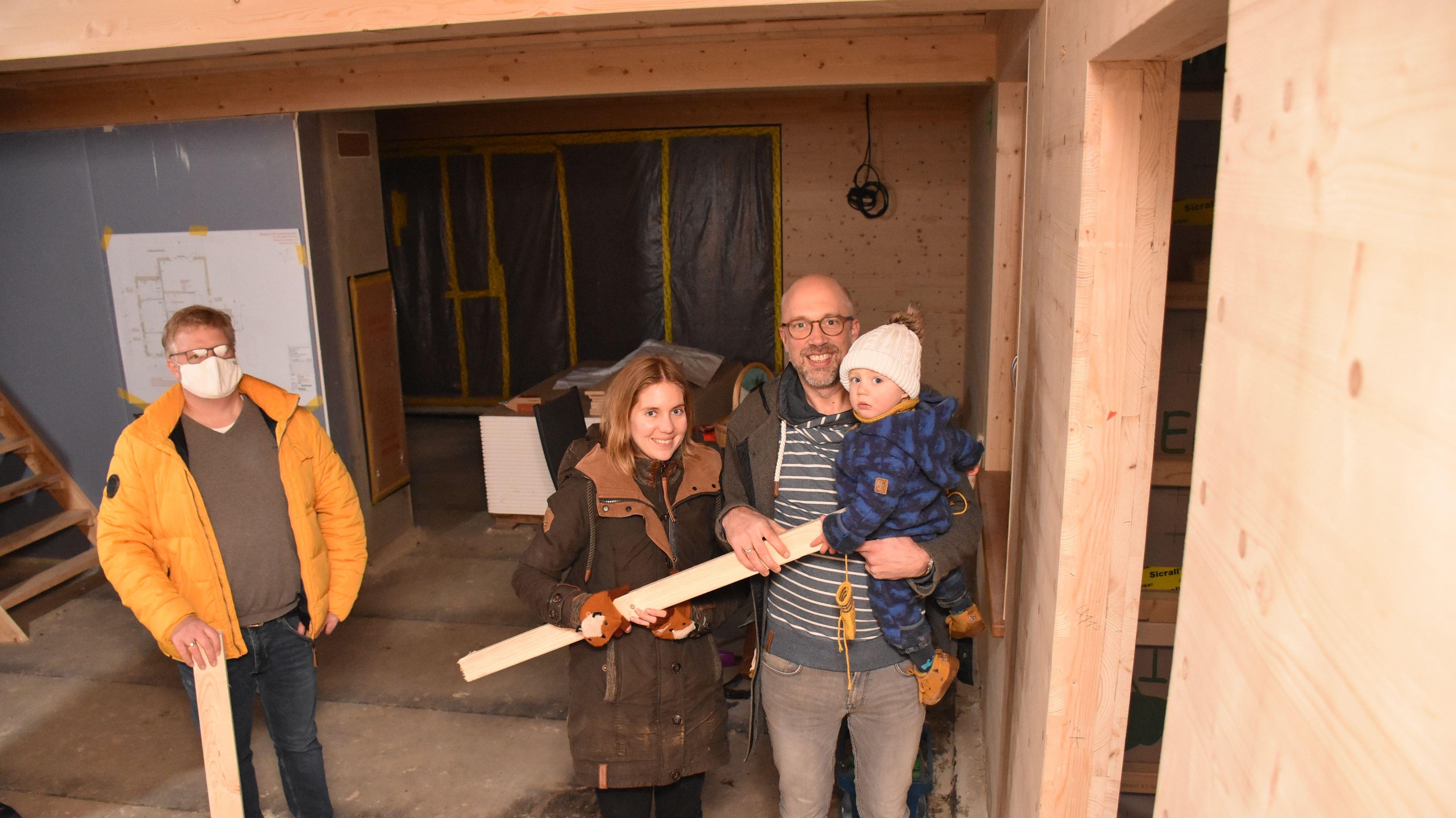 Sebastian und Laura Speckmann, im Bild mit Sohn Franz, freuen sich auf den Einzug in ihr nachhaltiges Eigenheim. Mario Drees (Zimmerer Profibau) leitet den Neubau und berät die Familie bei dem Projekt. Foto: Timphaus