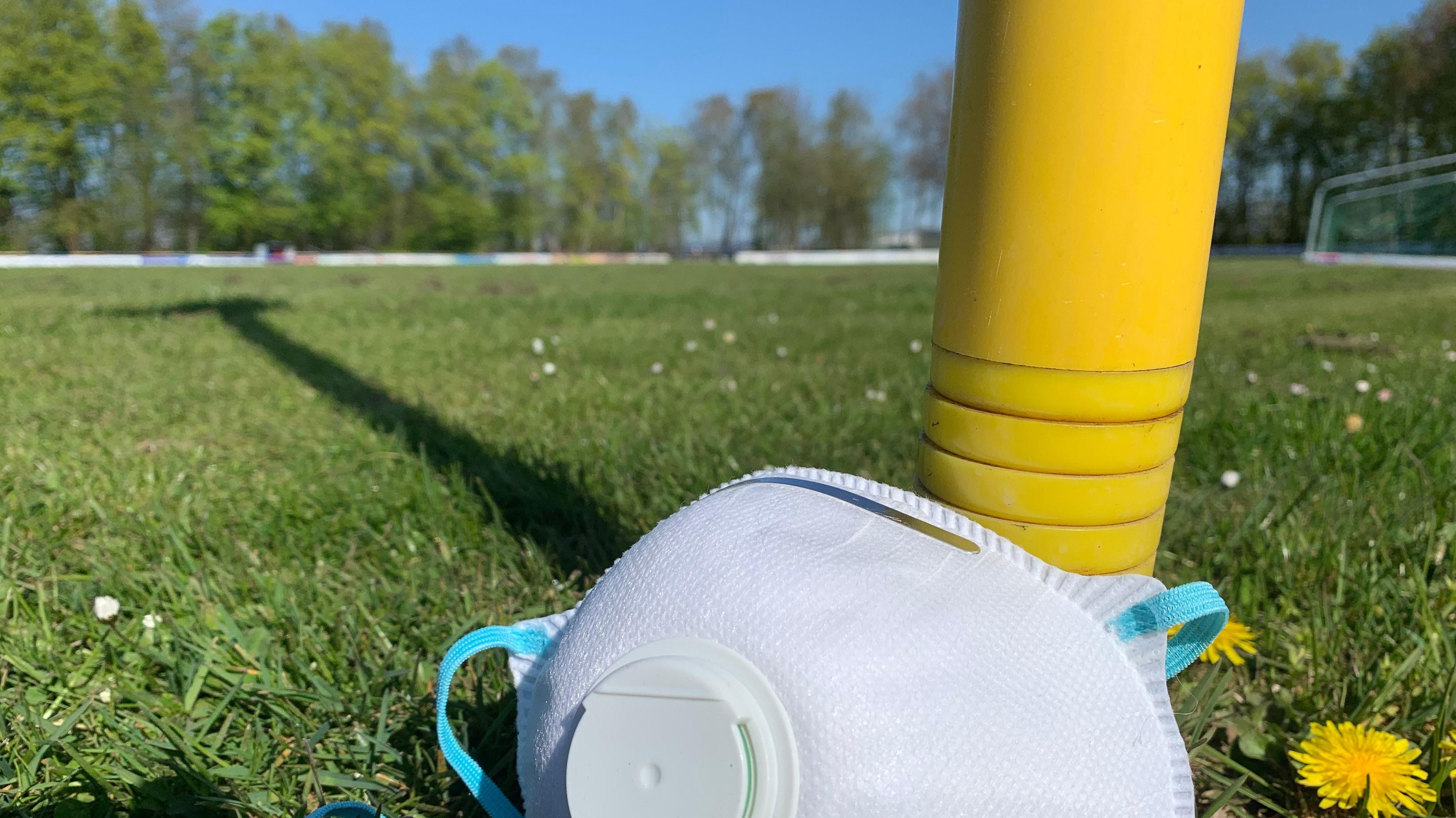 Symbol der Zeit: Maske auf dem Fußballfeld. Foto: Lünsmann