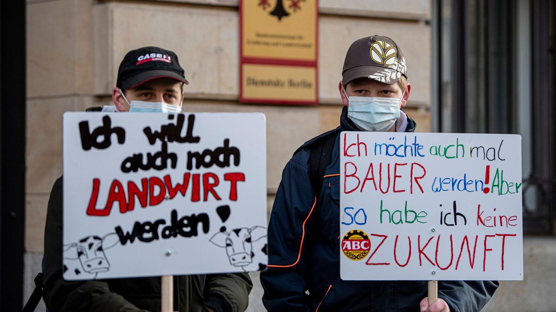Zwei junge angehende Landwirte demonstrieren mit Plakaten vor dem Bundeslandwirtschaftsministerium für höhere Preise für Agrarprodukte und weniger Regulierung. Foto:dpa/Fabian Sommer