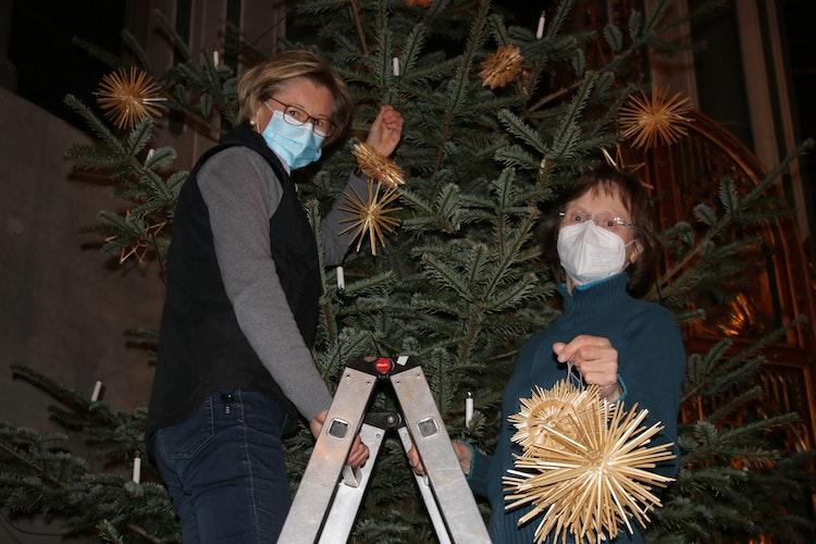 Stellenweise hoch hinaus: Monika König (links) und Brigitte Bohne nahmen die Strohsterne von den Bäumen ab. Foto: Lammert