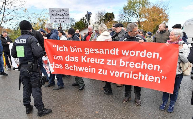 Erfurter demonstrieren während der Grundsteinlegung für eine neue Moschee mit einem Plakat mit der Aufschrift Ich bin gesandt worden, um das Kreuz zu brechen, das Schwein zu vernichten. Foto: dpaSchutt