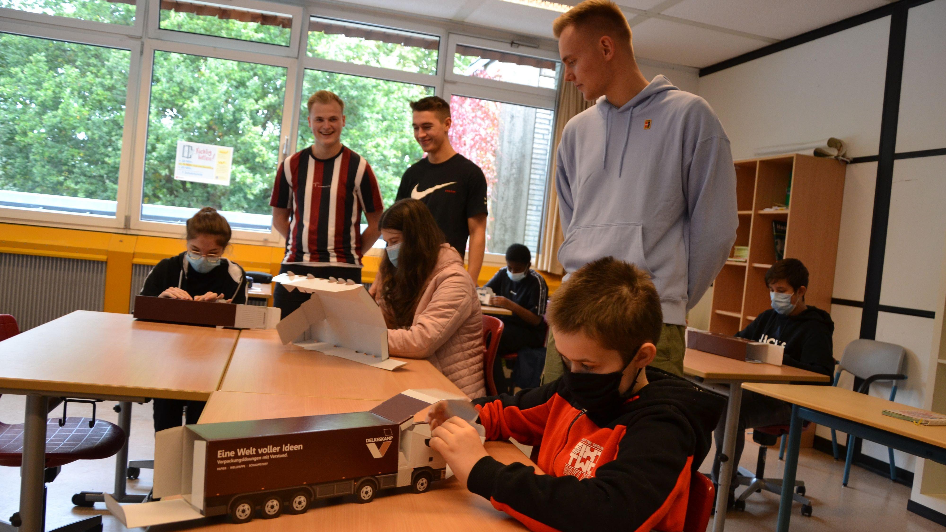 Gebastelt wurde auch: Die Auszubildenden Thomas Eveslage, Marlon Gärtner und Jan Ellers (von links, stehend) hatten den Schülern Faltsets mitgebracht.  Foto: G. Meyer