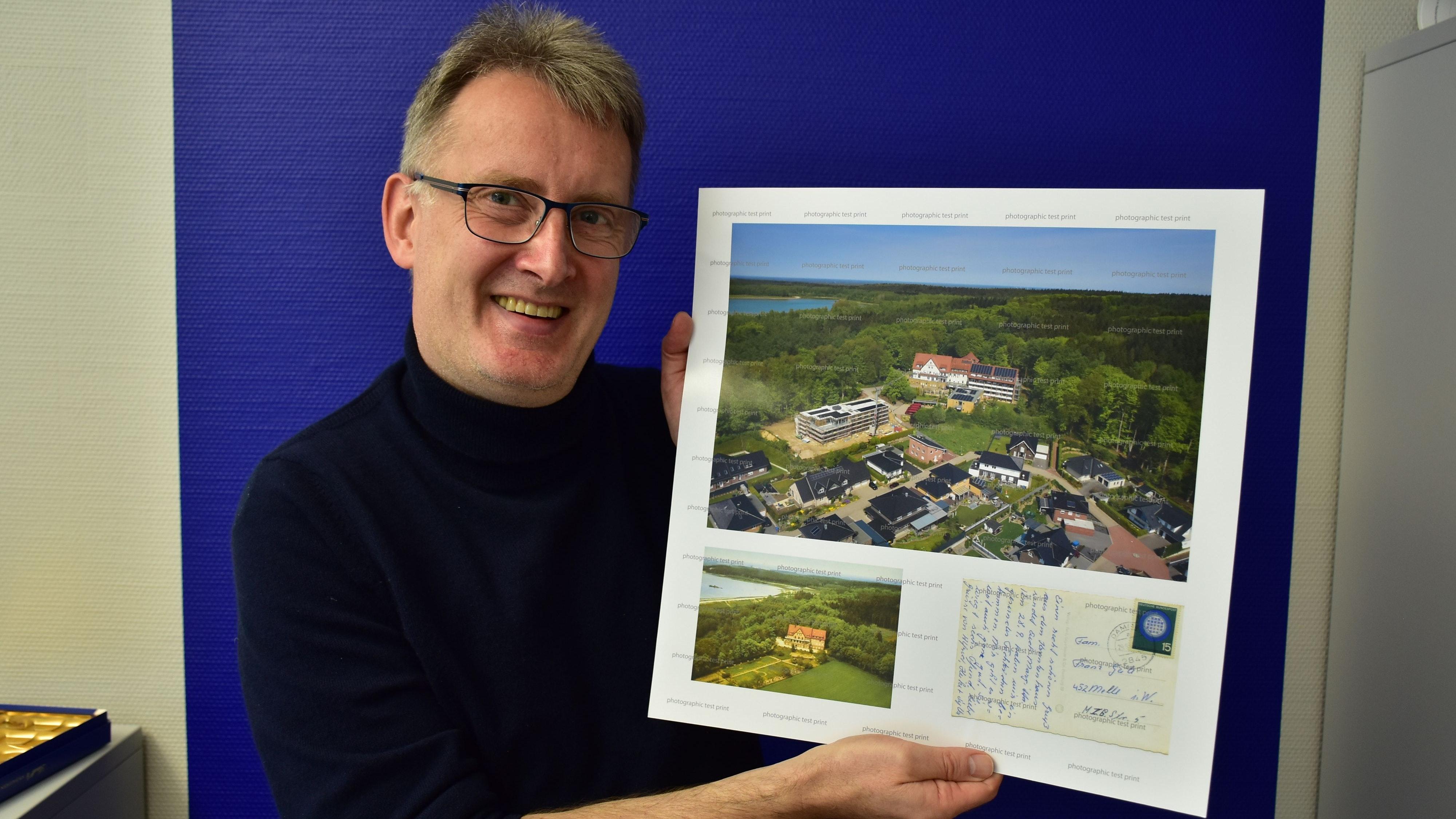 Neu und alt: Martin von den Driesch zeigt eines der Kalenderblätter mit 2 Ansichten des Seniorenheims Haus Maria-Rast mit seiner früheren und heutigen Umgebung. Foto: Lammert
