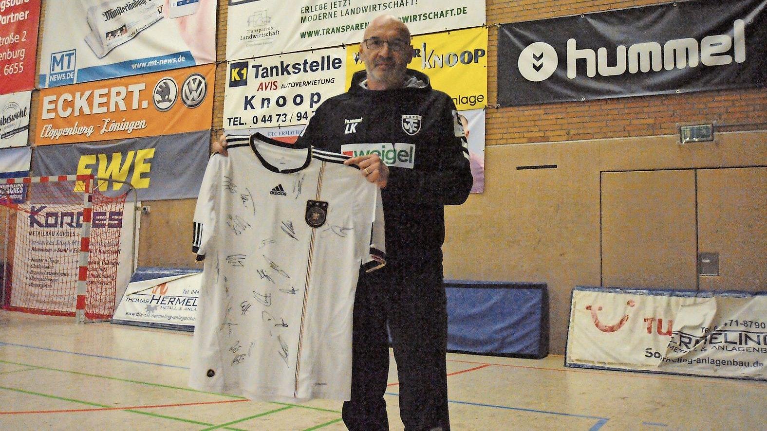 Wertvolles Exemplar: Leszek Krowicki, Coach der TVC-Handballer, möchte sich zugunsten des guten Zwecks von einem Trikot des früheren Fußball-Nationalspielers Per Mertesacker trennen. Foto: Bettenstaedt
