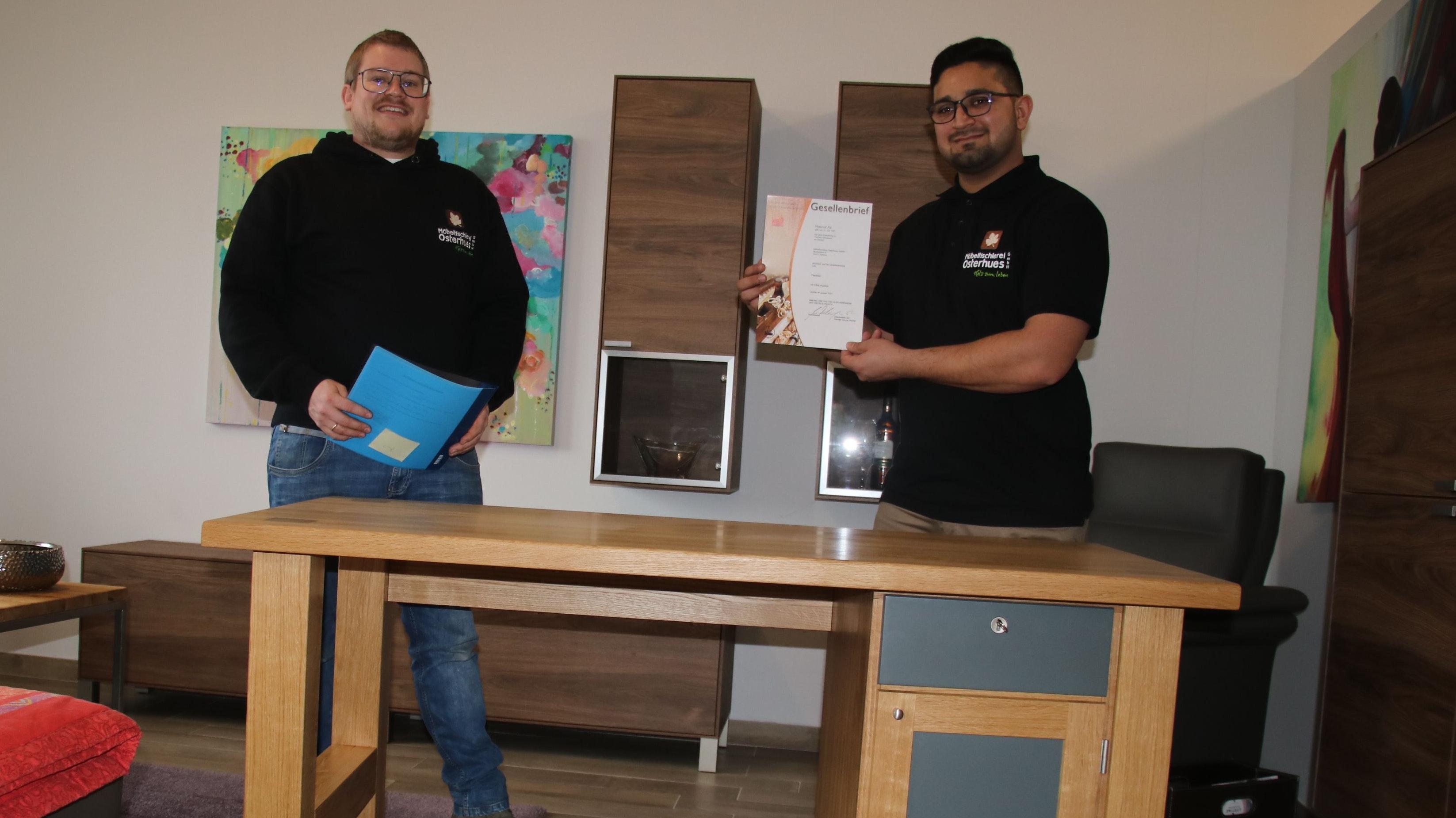 Fast schon ein Meisterstück: Jan Osterhues (links) freut sich mit seinem ehemaligen Auszubildenden Hasnat Ali über die bestandene Prüfung und den Schreibtisch, der er gebaut hat. Foto: Lammert