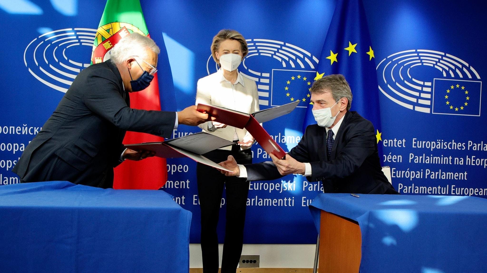 EU-Kommissionspräsidentin Ursula von der Leyen (M), schaut dabei zu, wie Portugals Premierminister Antonio Costa und EU-Parlaments-Präsident David Sassoli den Corona-Wiederaufbauplan unterzeichnen. Foto: dpa/Matthys