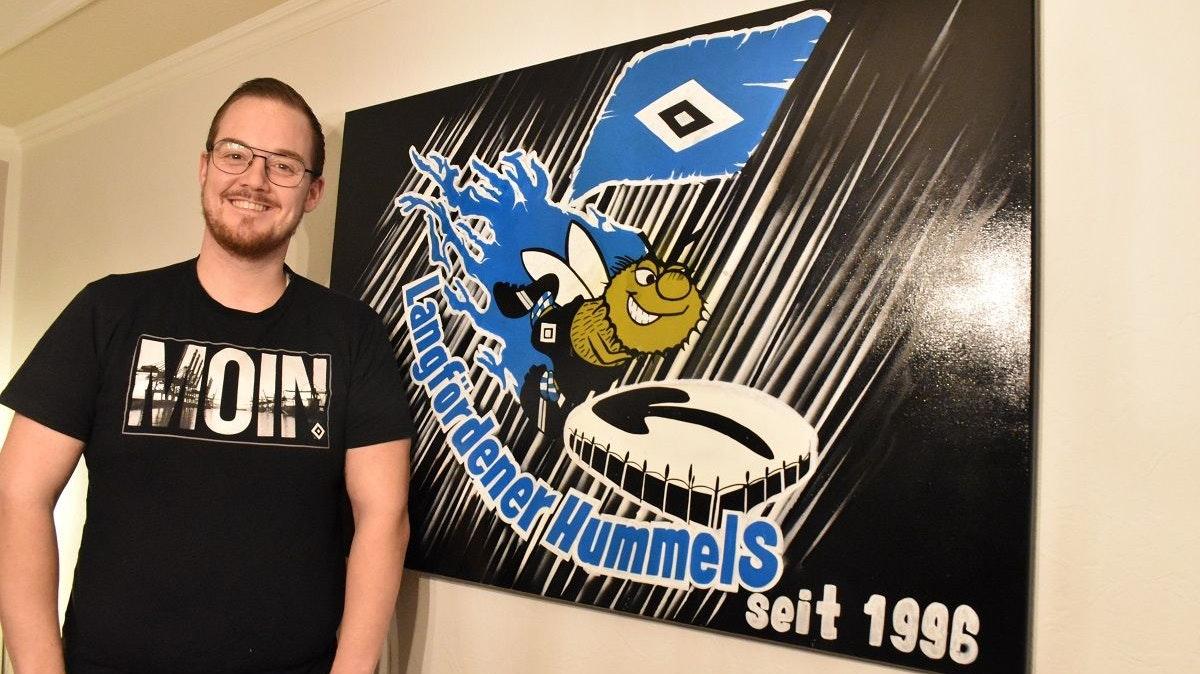 """Ist zuversichtlich, dass in diesem Jahr der Aufstieg gelingt: Tim Weustermann mit dem auf Leinwand gebrachten Logo des HSV-Fanclubs """"Langfördener Hummels"""". Foto: Klöker"""