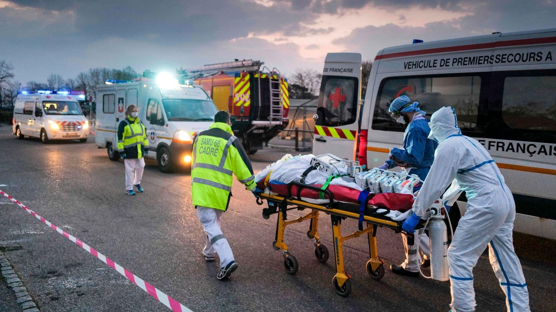 Medizinisches Notfallpersonal transportiert einen Patienten, der mit dem Coronavirus infiziert ist, von einem Militärkrankenhaus in Mulhouse zu einem Rettungswagen. Im Anschluss wird der Patient mit einem Hochgeschwindigkeitszug in eine andere Klinik verlegt. Foto: dpa/Bozon