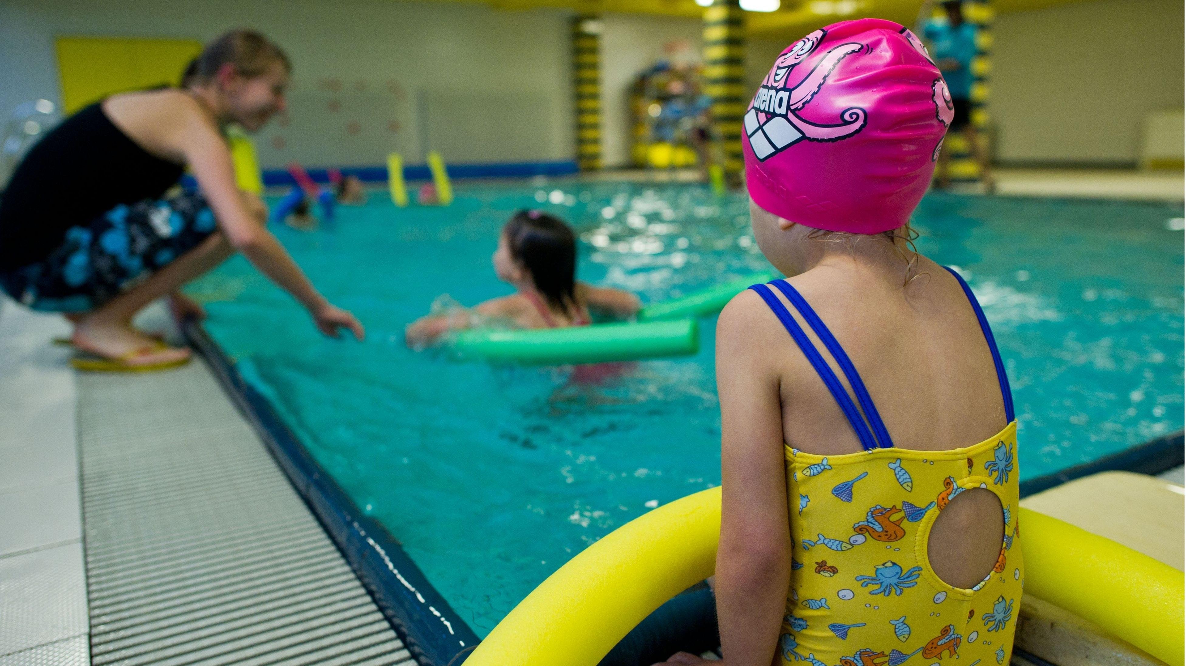 Mutig ins kühle Nass: Ehrenamtliche und Hauptamliche helfen Kindern, schwimmen zu lernen. Momentan allerdings bleiben alle auf dem Trockenen. Symbolbild: dpa