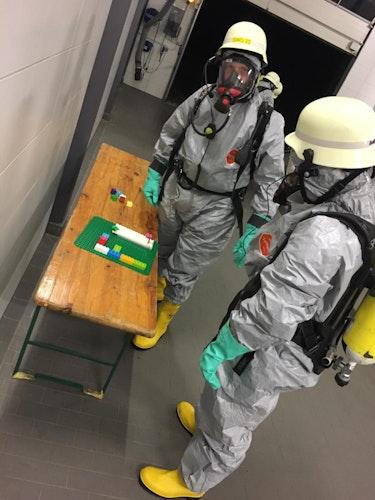 Kein Spiel, sondern Übung für den Ernstfall: In Chemikalienschutzanzügen musste mit Duplo-Steinen ein vorgegebenes Muster nachgebaut werden. Foto: Feuerwehr
