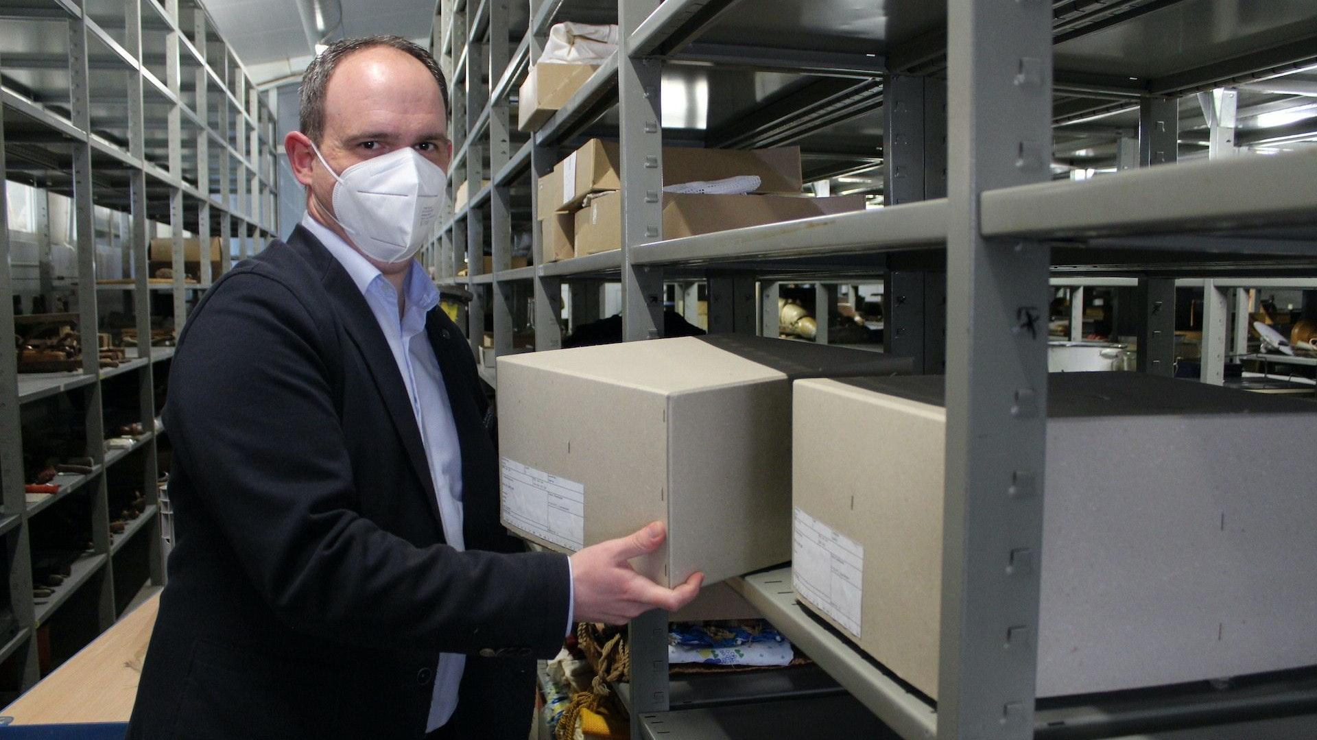 """Kai Jansen räumt die Funde aus der Grabung im Baugebiet """"Am Telbraker Esch"""" in die Regale des Klimamagazins des Museums Vechta. Foto: Heinzel"""