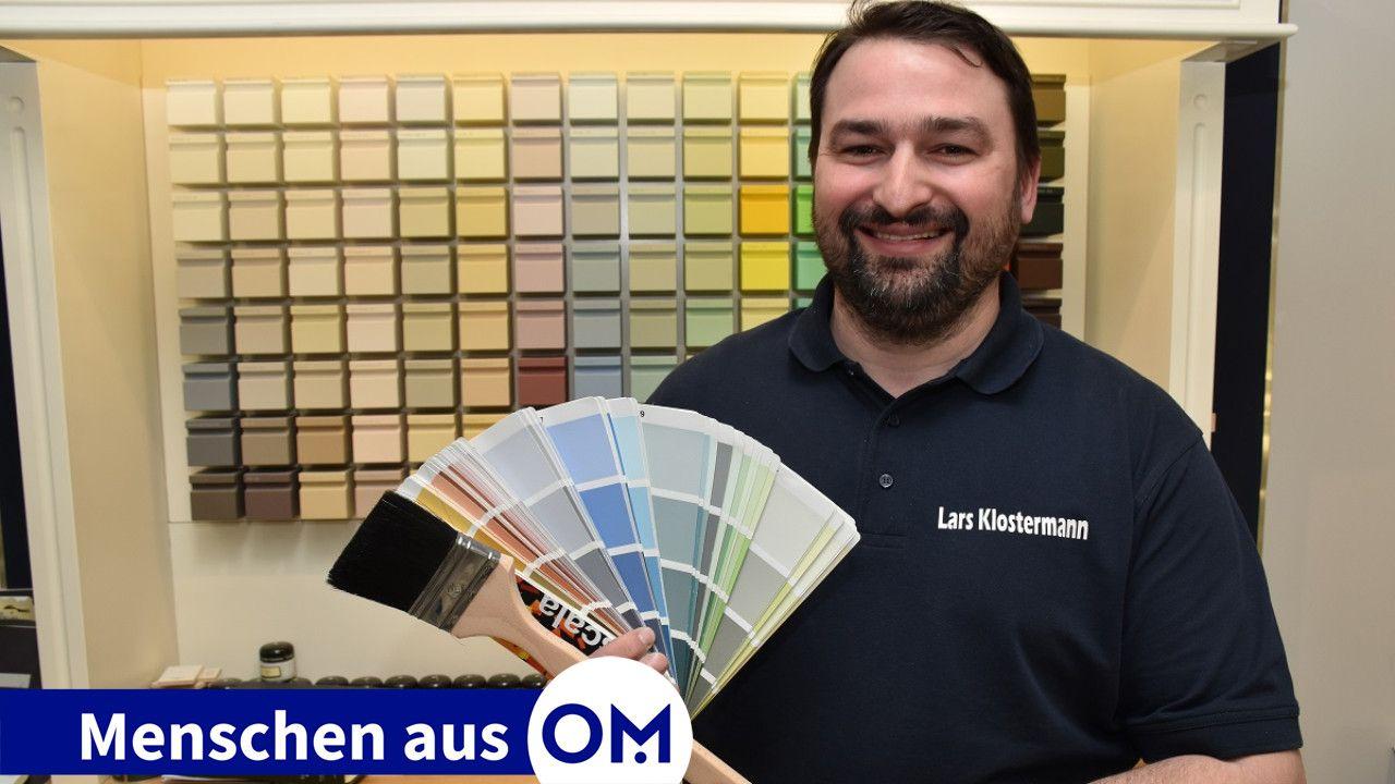 Mit Pinsel und Farbtonkarte: Lars Klostermann in seiner Ausstellung. Foto: Klöker