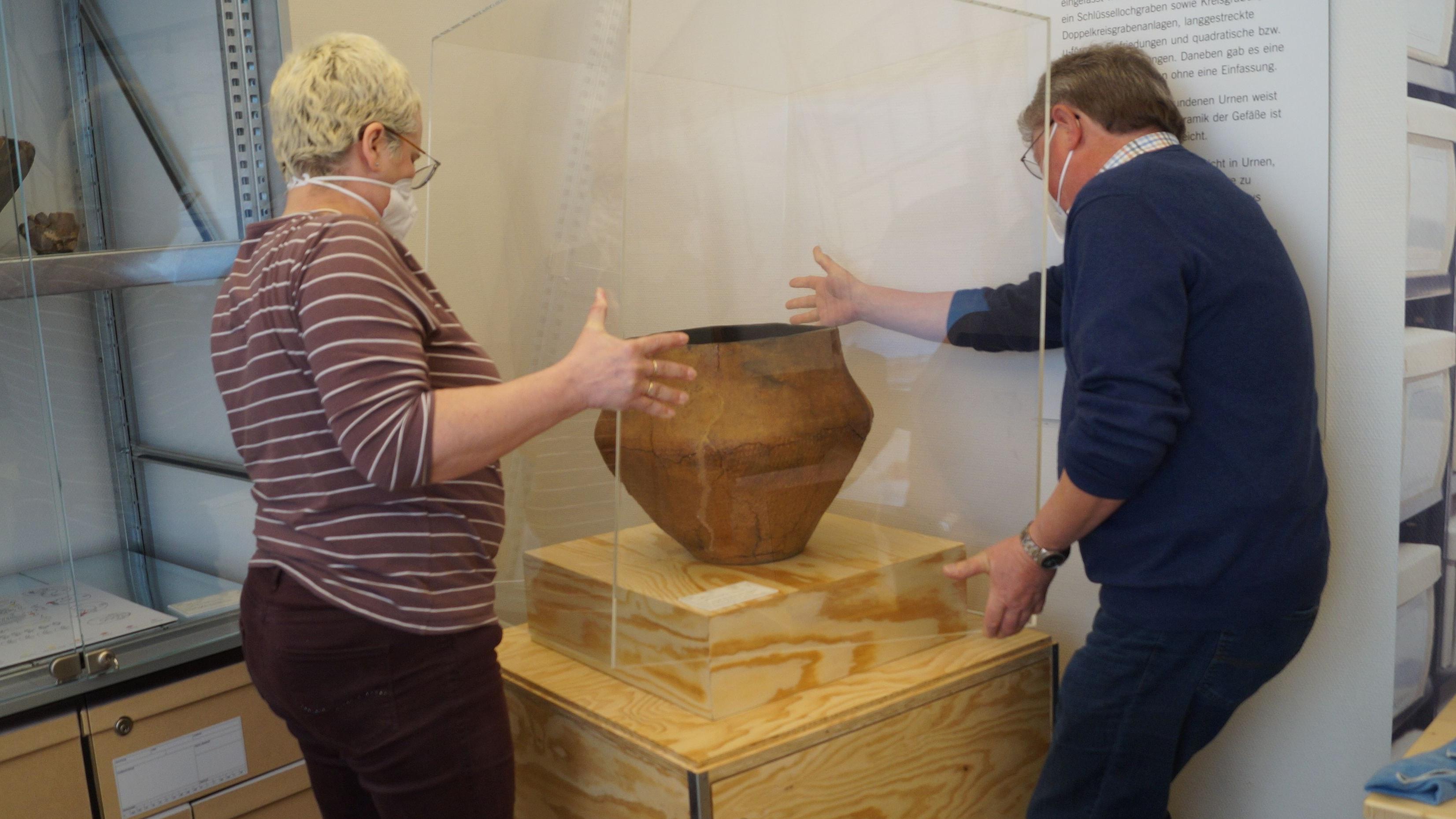 Rund 3.000 Jahre alt: Eine große Urne aus der Bronzezeit hat nun ihren Platz im ArchäoVisbek gefunden. Museumsberaterin Dr. Beate Bollmann und Manfred Gelhaus vom Heimatverein Visbek setzen das Fundstück angemessen in Szene. Foto: C. Meyer