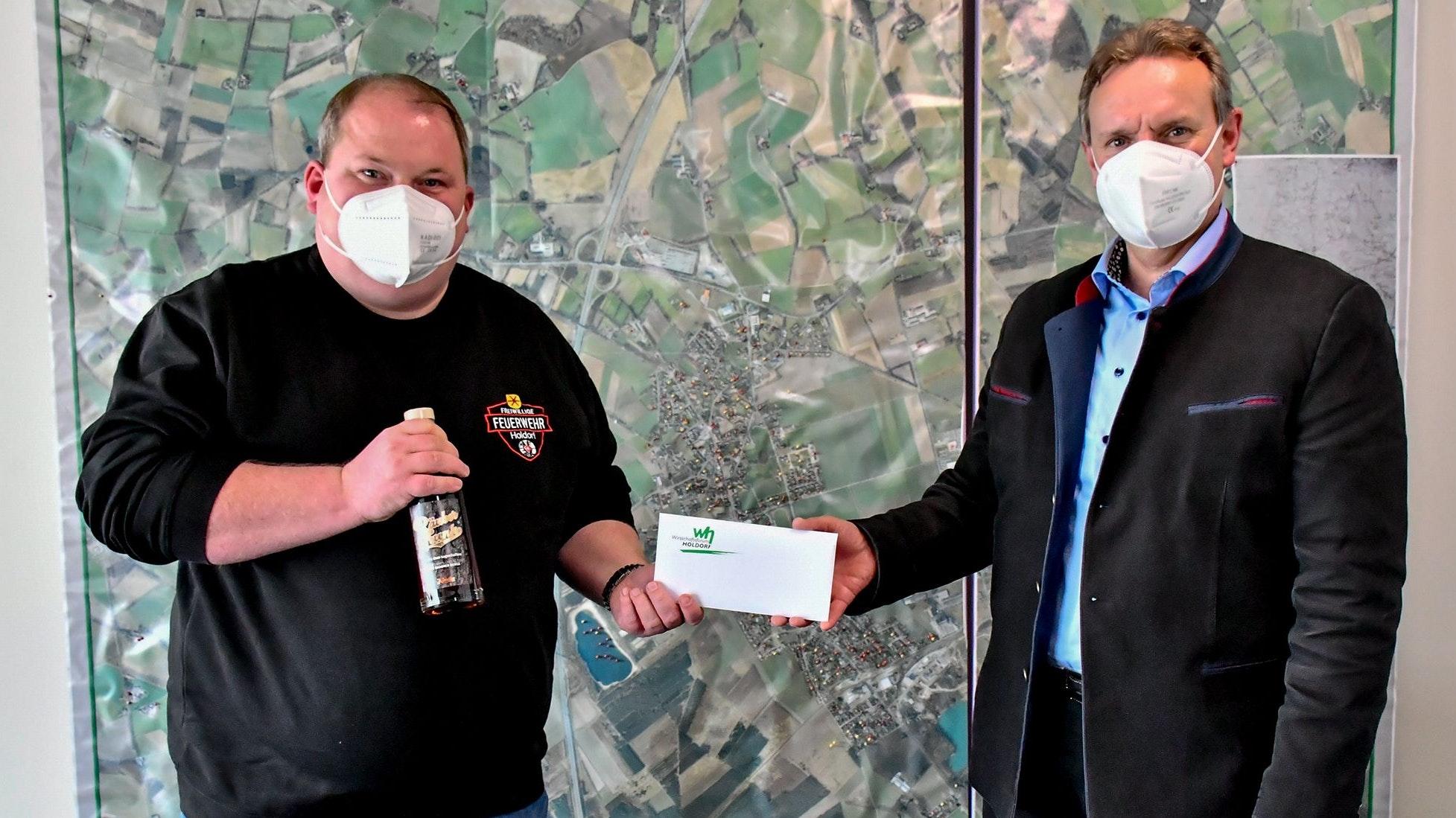 Ein Coronaheld (links): Bürgermeister Dr. Wolfgang Krug (rechts) dankt Jens Lindemann mit einer Flasche Räubertrunk und einem Gutschein des Holdorfer Wirtschaftsforums für den engagierten Einsatz. Foto: Vollmer