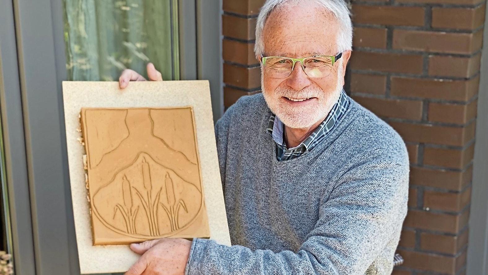 Mit dem Neuscharreler Wappen: Herbert Bley zeigt die Tontafel, die noch gebrannt werden muss. Foto: Claudia Wimberg
