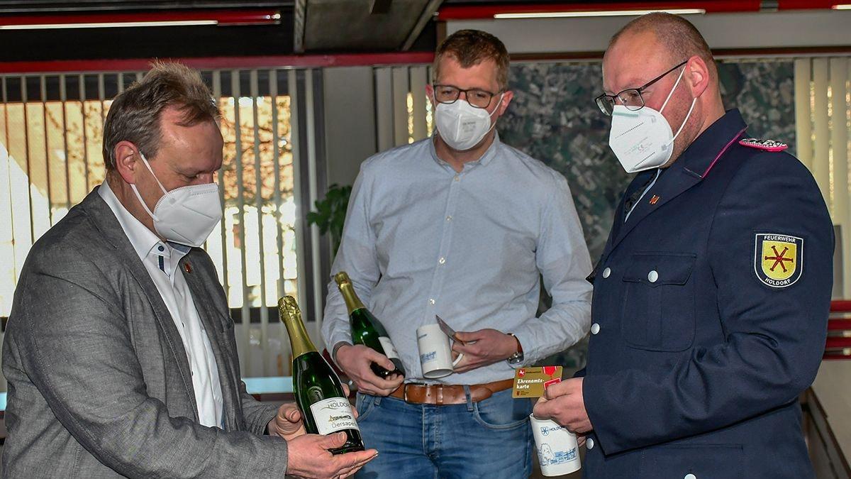 Dankeschön: Bürgermeister Dr. Wolfgang Krug überreicht jeweils die Ehrenamtskarte mit Holdorf-Becher und einer Flasche Dersaperle an Dirk Völkerding und Daniel Fraß (von links). Foto: Vollmer