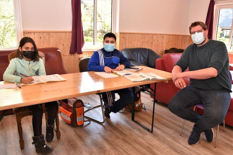 Ihnen gefällt es im Jugendtreff sehr gut: Die Geschwister Maram und Mohammed Almawas machen, unterstützt von Jugendpfleger Timo Tatje, ihre Hausaufgaben. Foto: Böckmann